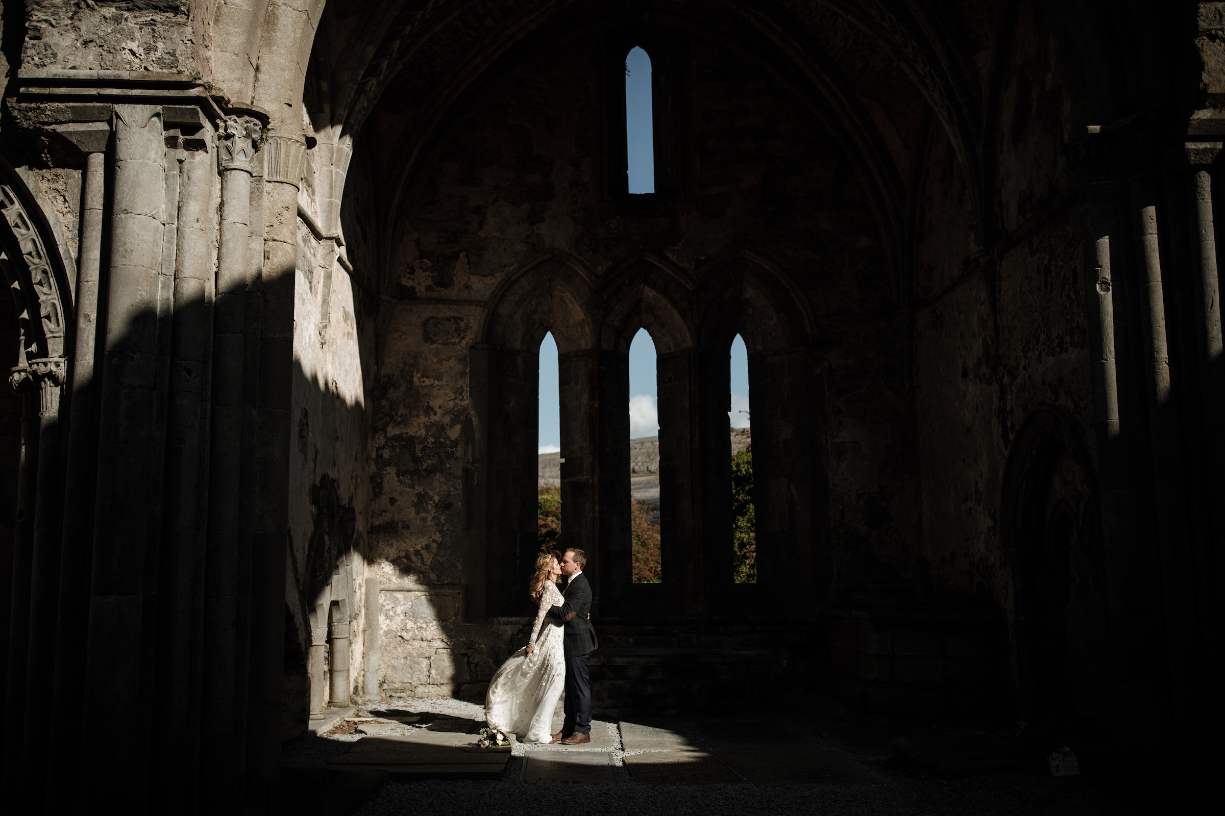 couple kissing in sunlight inside ruined cathedral - photo by White Cat Studio