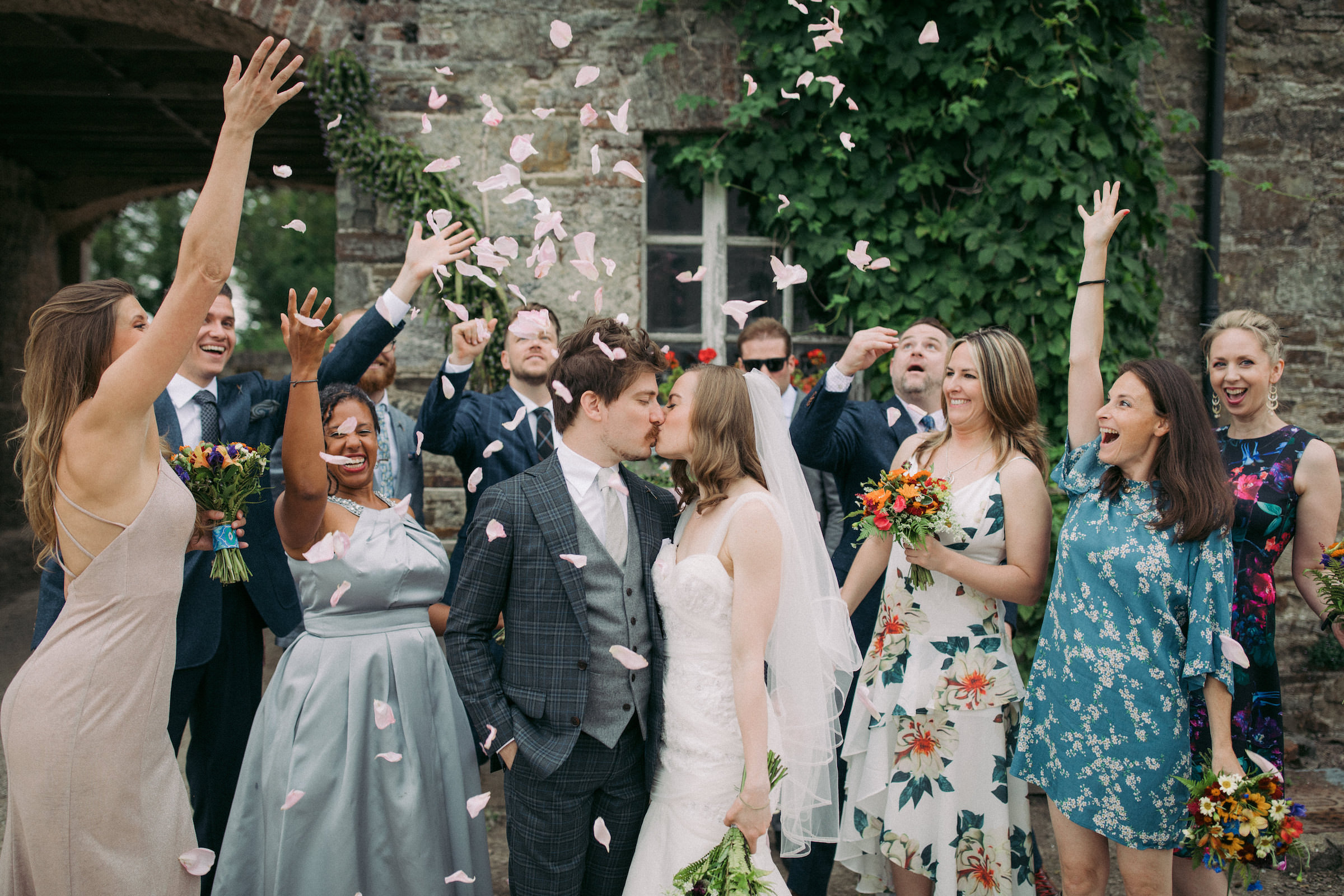 Friends throw rose petals on couple while they kiss - photo by White Cat Studio