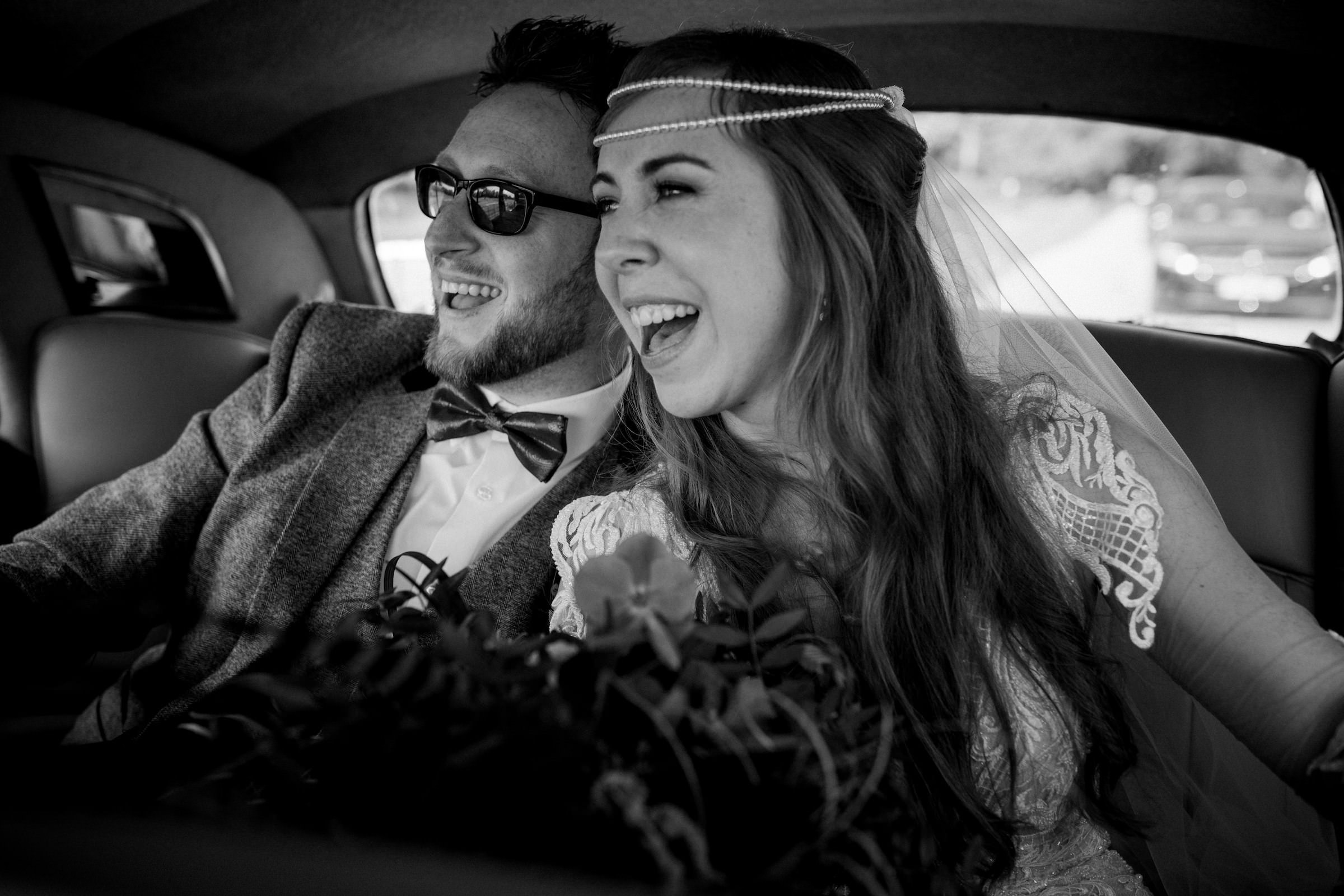 Happy couple in back of limousine - photo by White Cat Studio