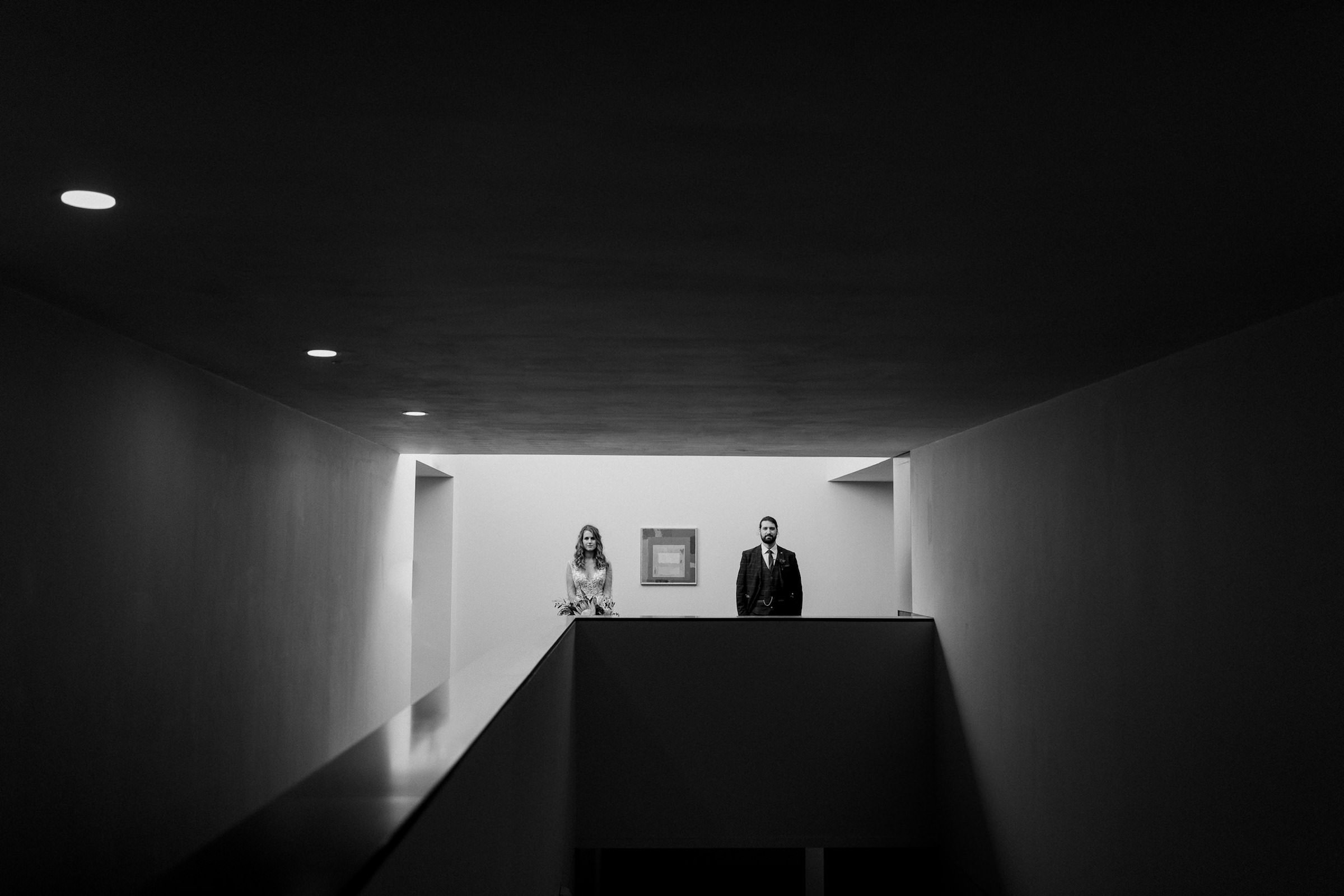 modern composition of bride and groom in apartment hallway - photo by White Cat Studio