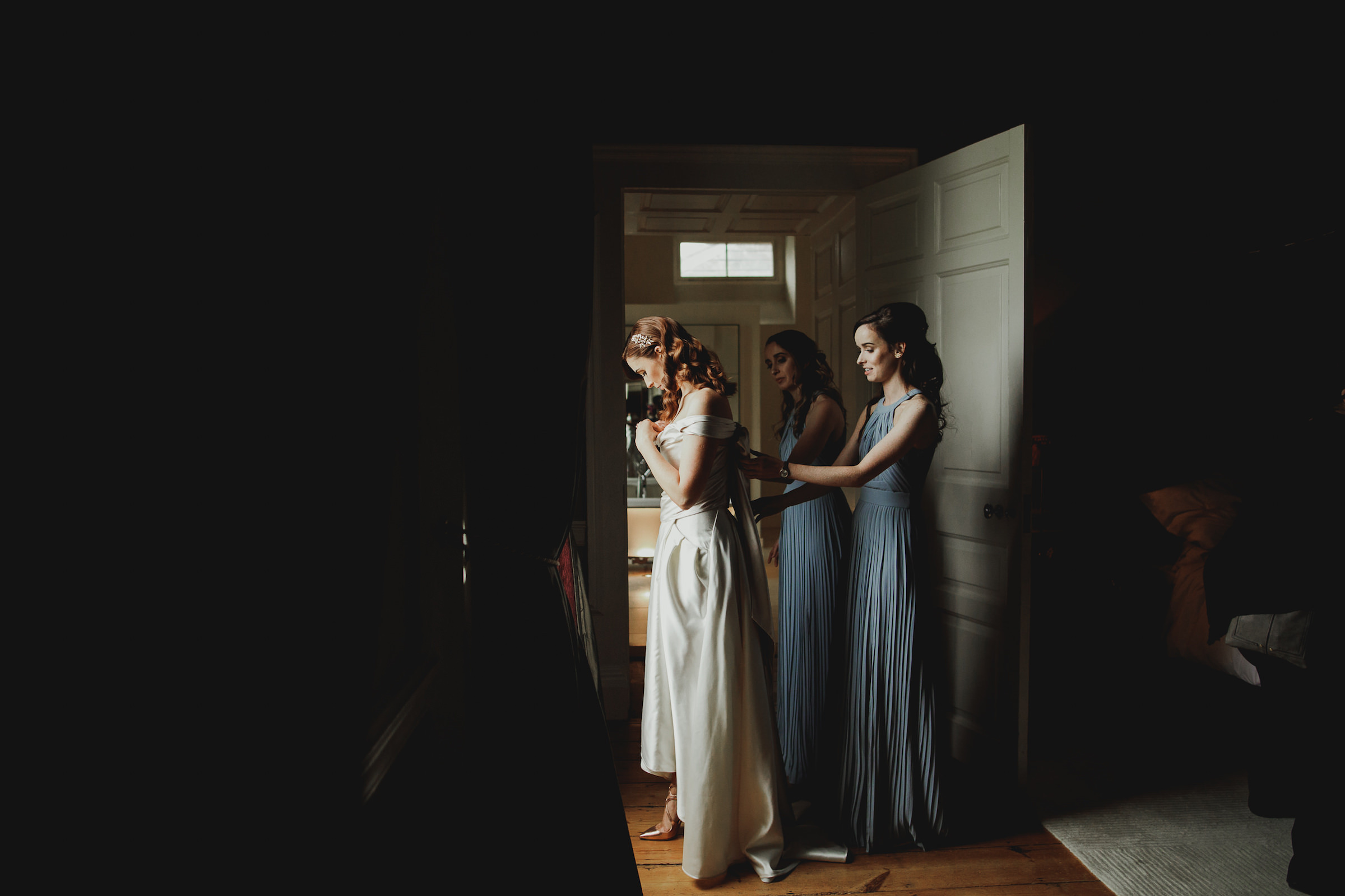 Red haired bride getting ready with bridesmaids - photo by White Cat Studio