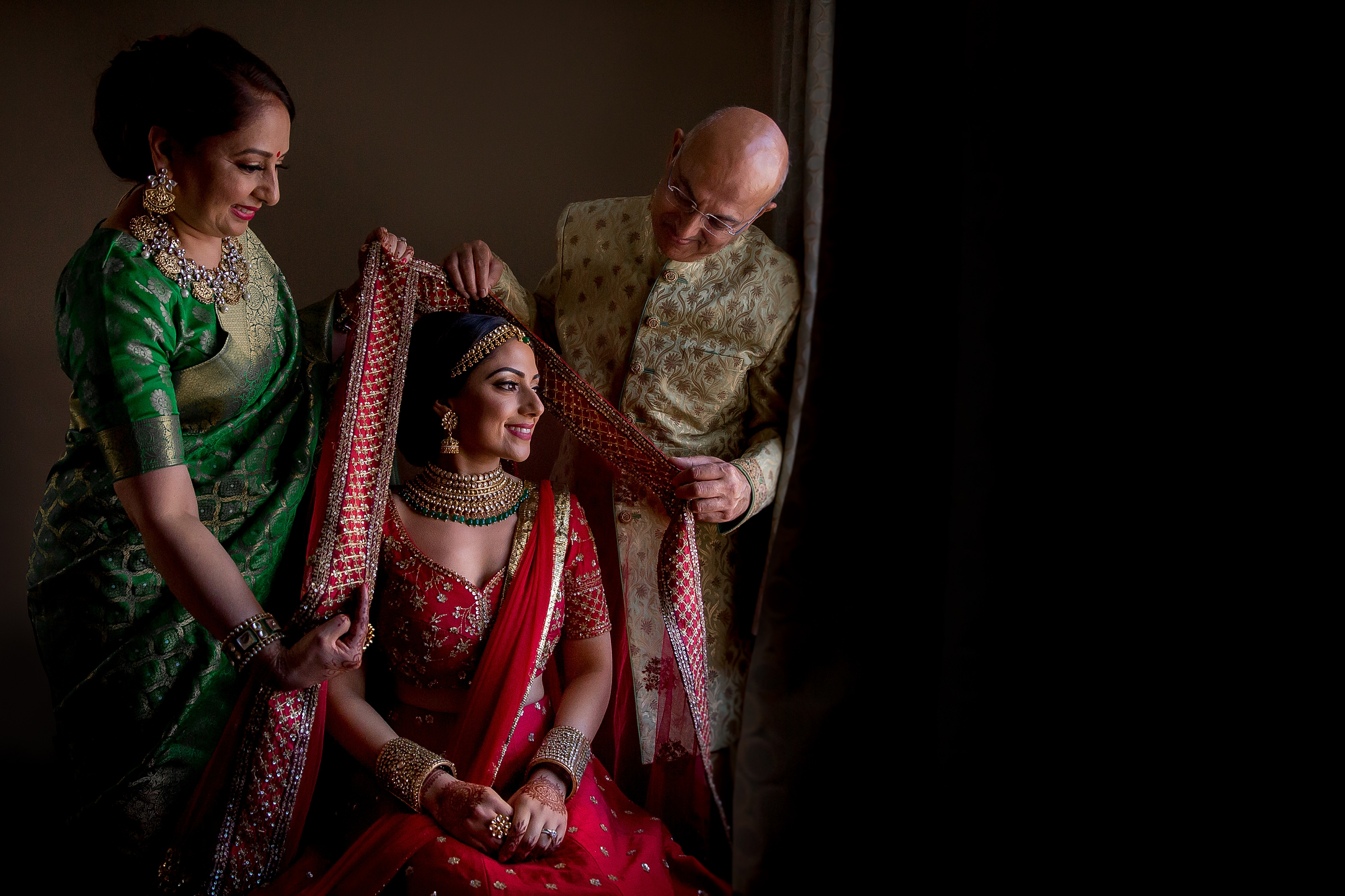 Brides parents with seated bride - photo by Apresh Chavda Photography