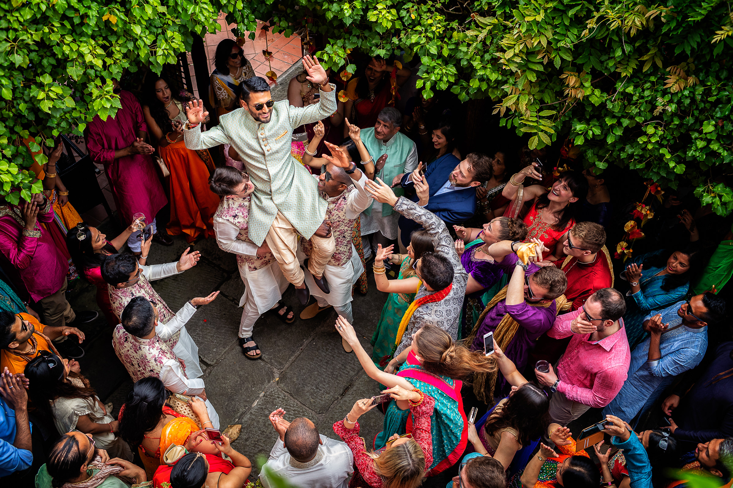 Aerial view of groomsmen carrying the groom aloft amid colorful crowd of guests - photo by D2 Photography