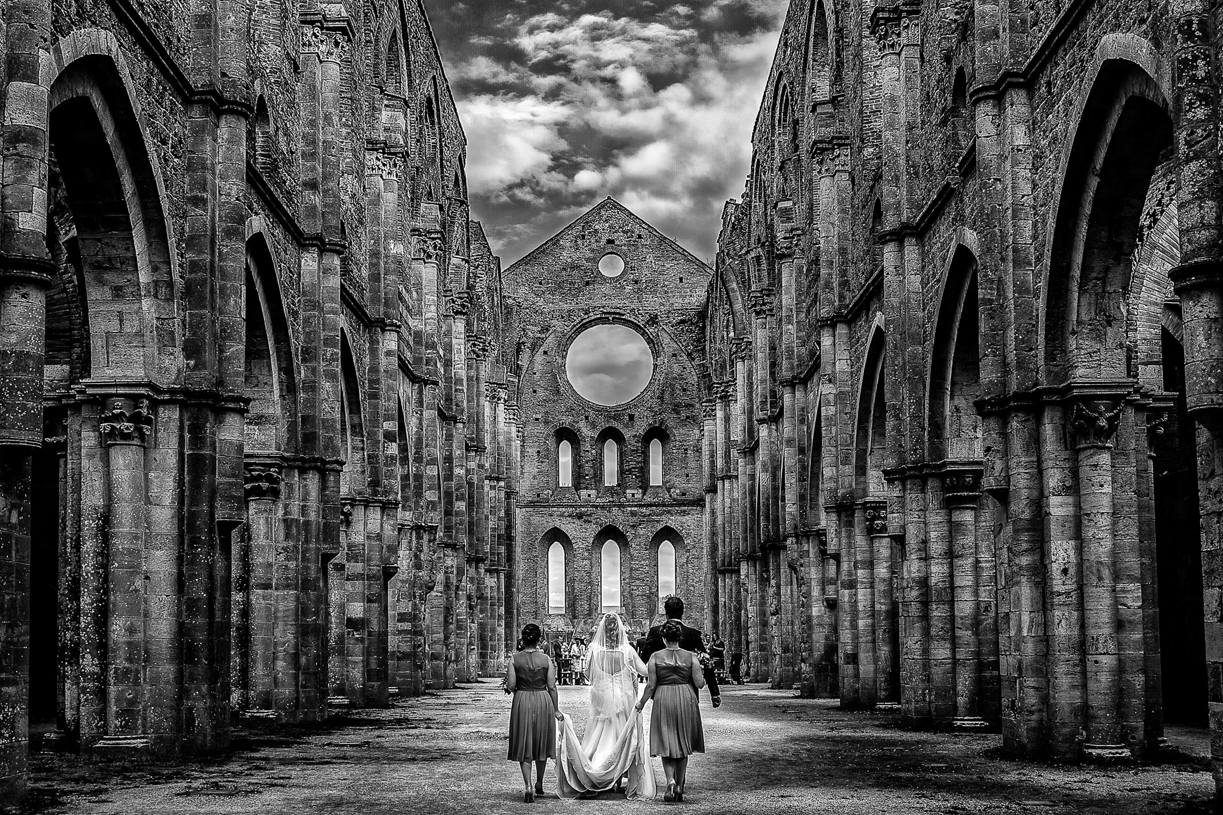 Bride and groom walk up aisle in under dramatic skies - photo by D2 Photography