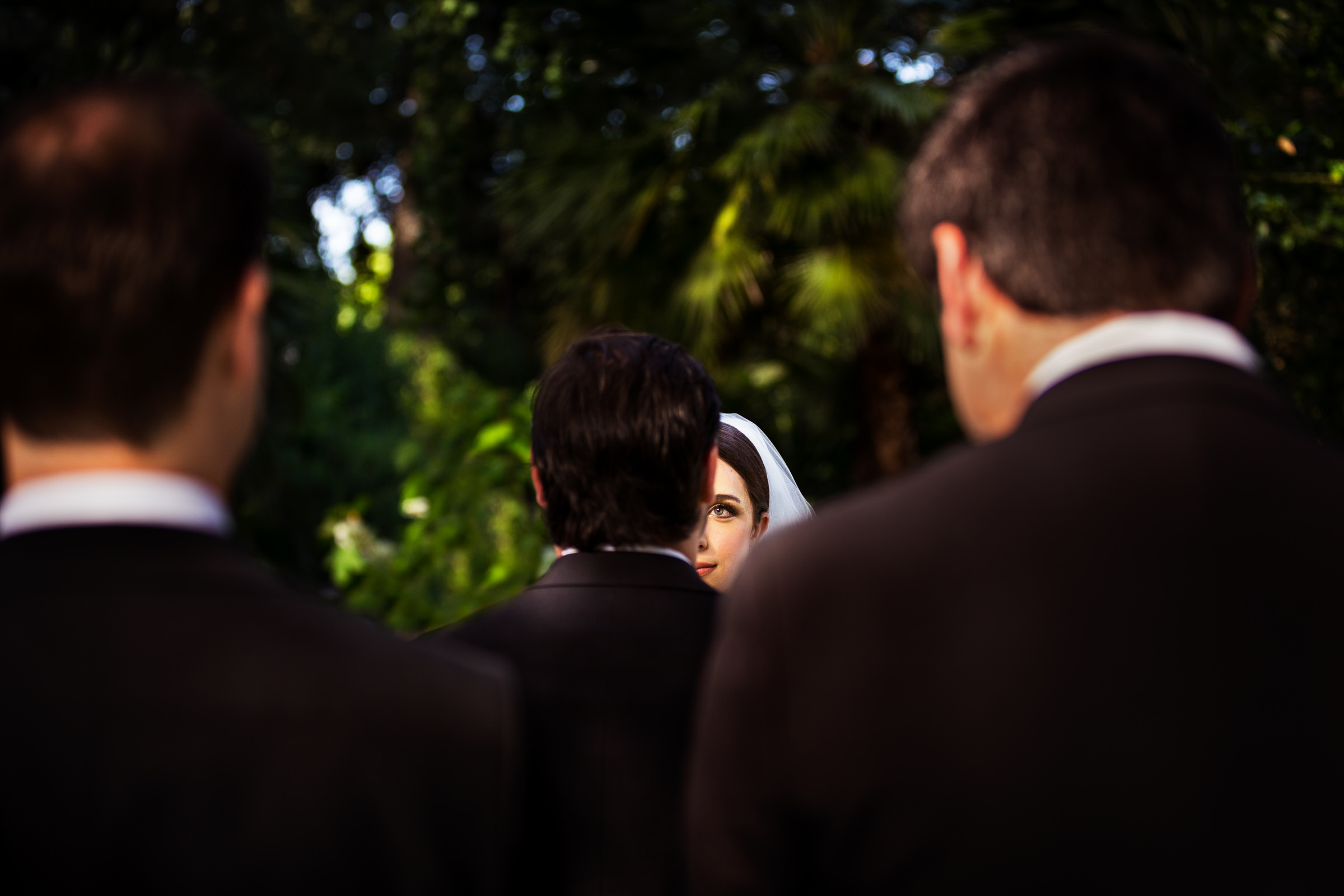 Bride seen through layers of suited men - photo by D2 Photography