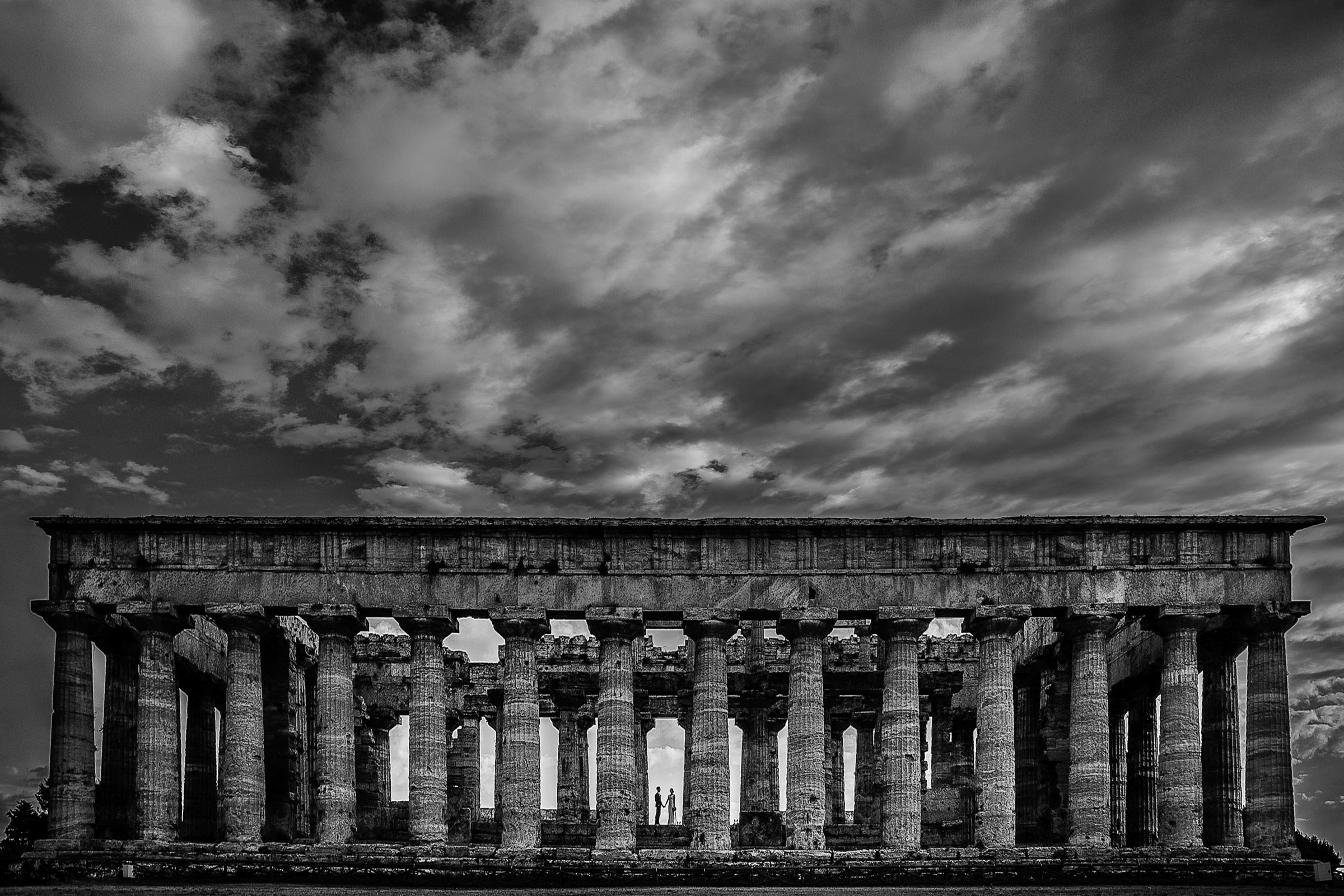 Couple silhouette at roman temple under stormy skies - photo by D2 Photography