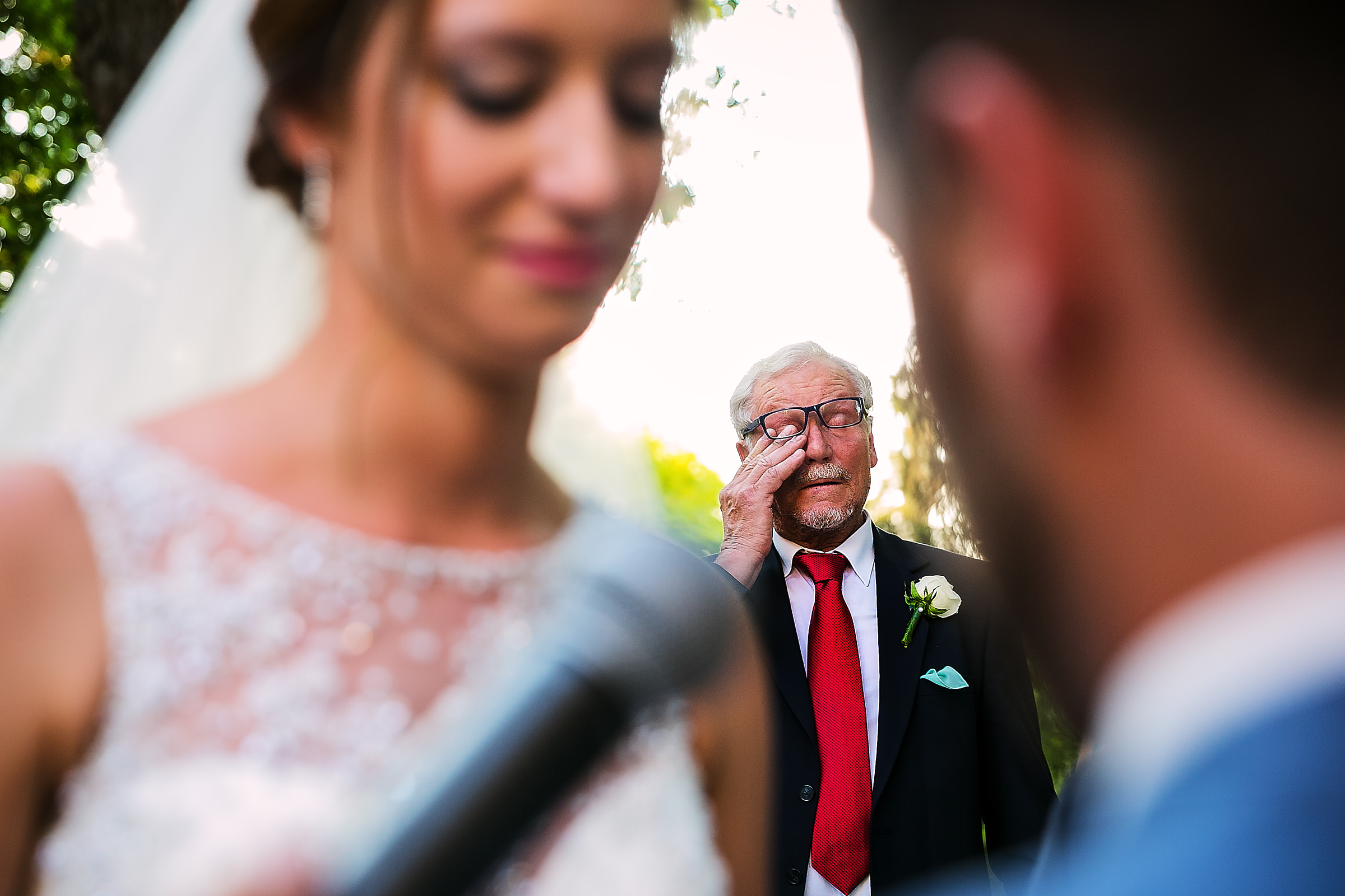 Father wipes a tear at ceremony - photo by D2 Photography