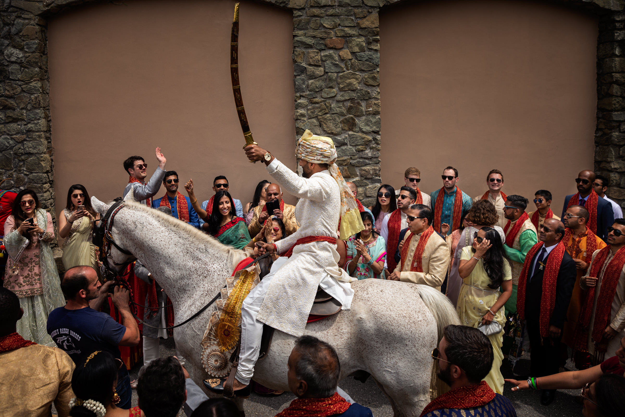Indian groom on horseback against crowd of guests - photo by D2 Photography