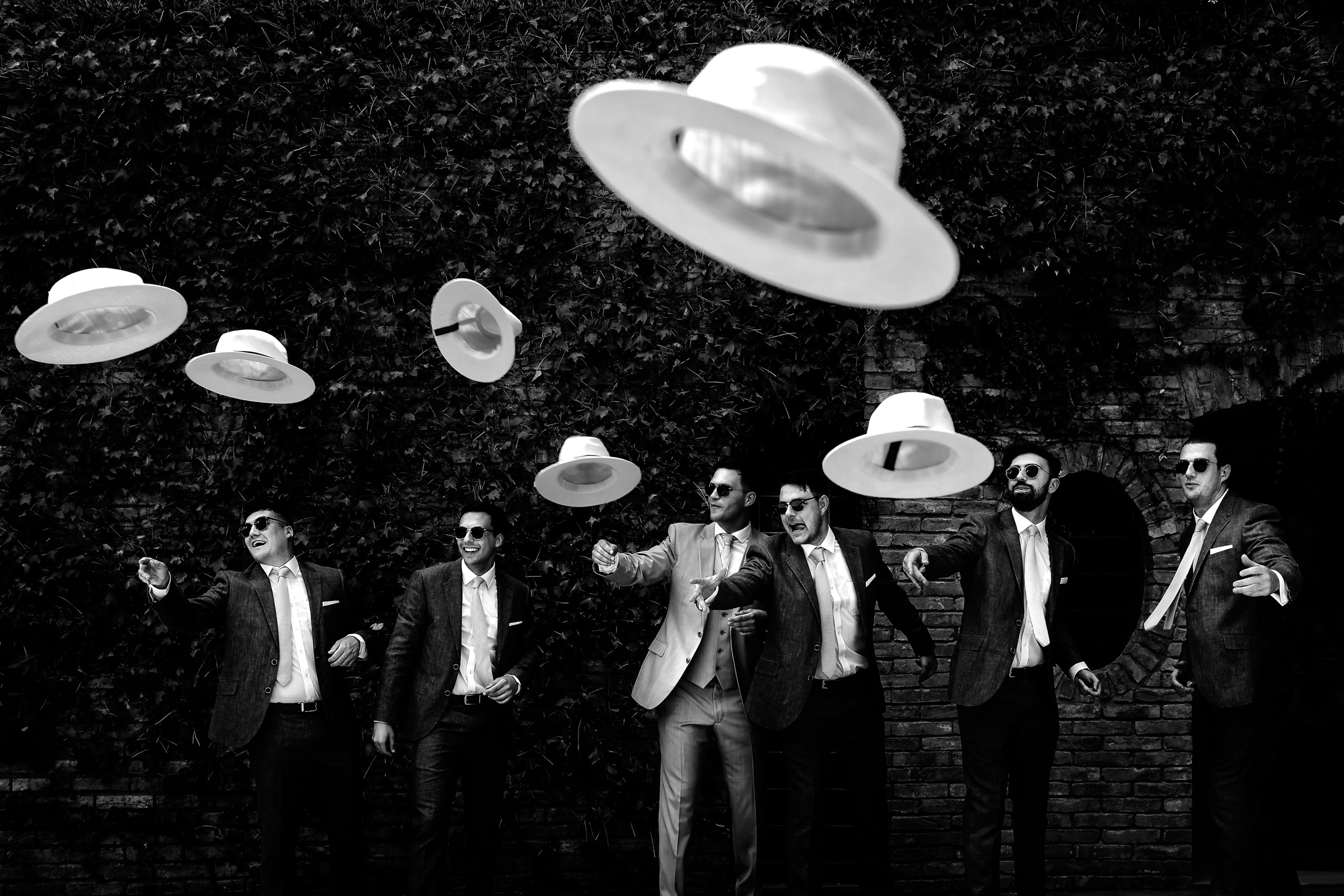 Photos of groomsmen throwing their hats - photo by D2 Photography
