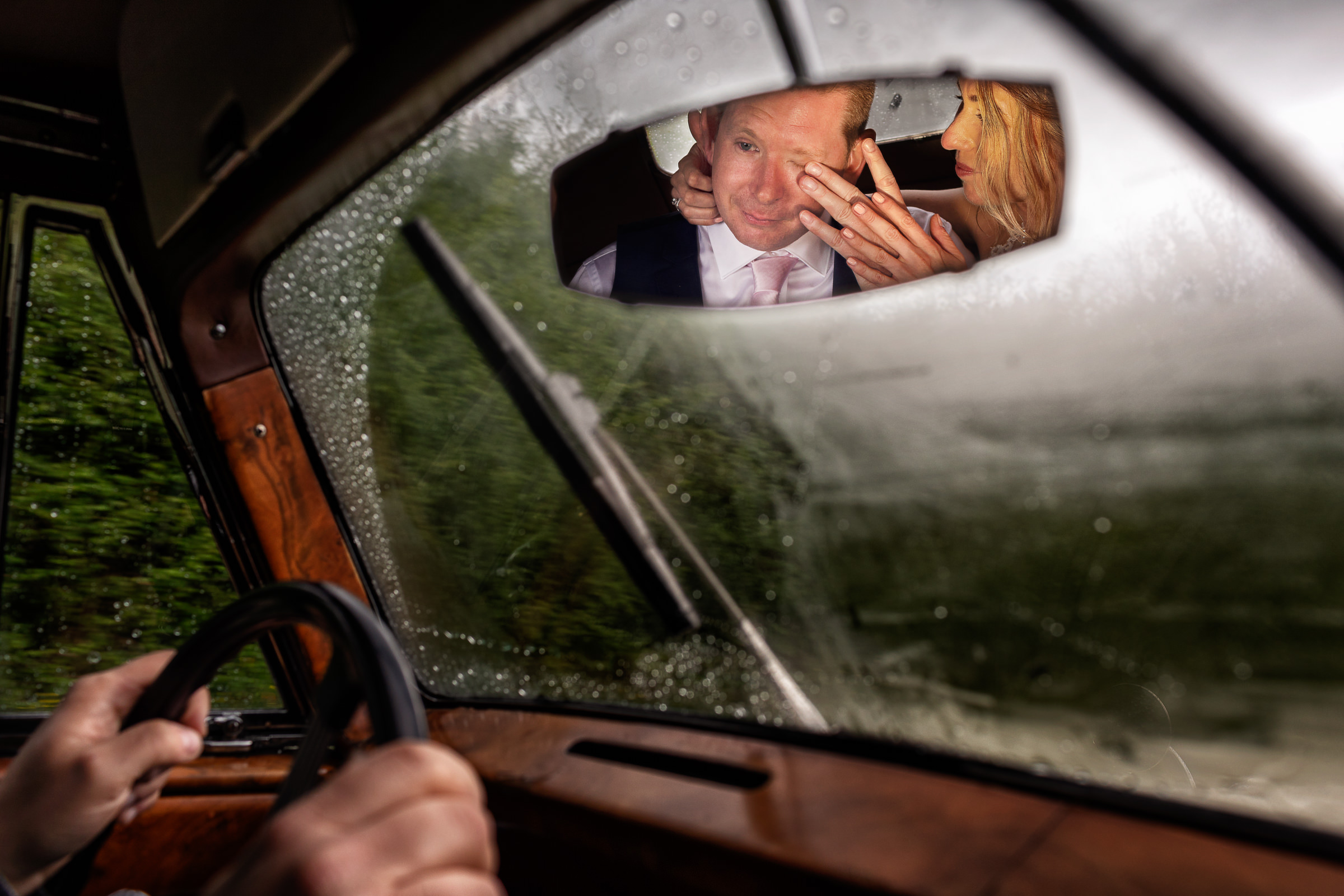 Rear view mirror reflection of bride wiping grooms tears - photo by D2 Photography