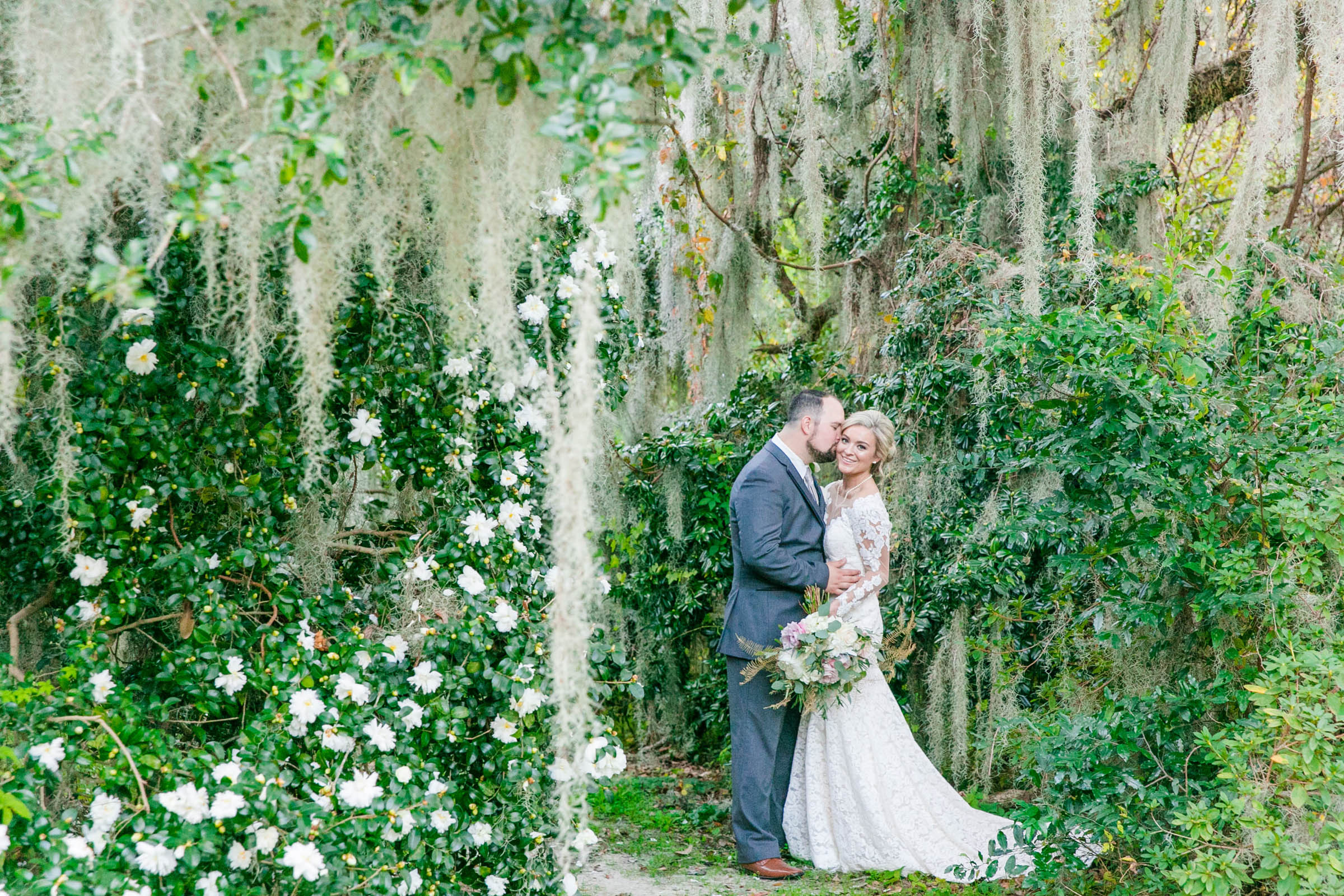 Couple kiss in spanish moss fairytale setting - photo by Dana Cubbage Weddings