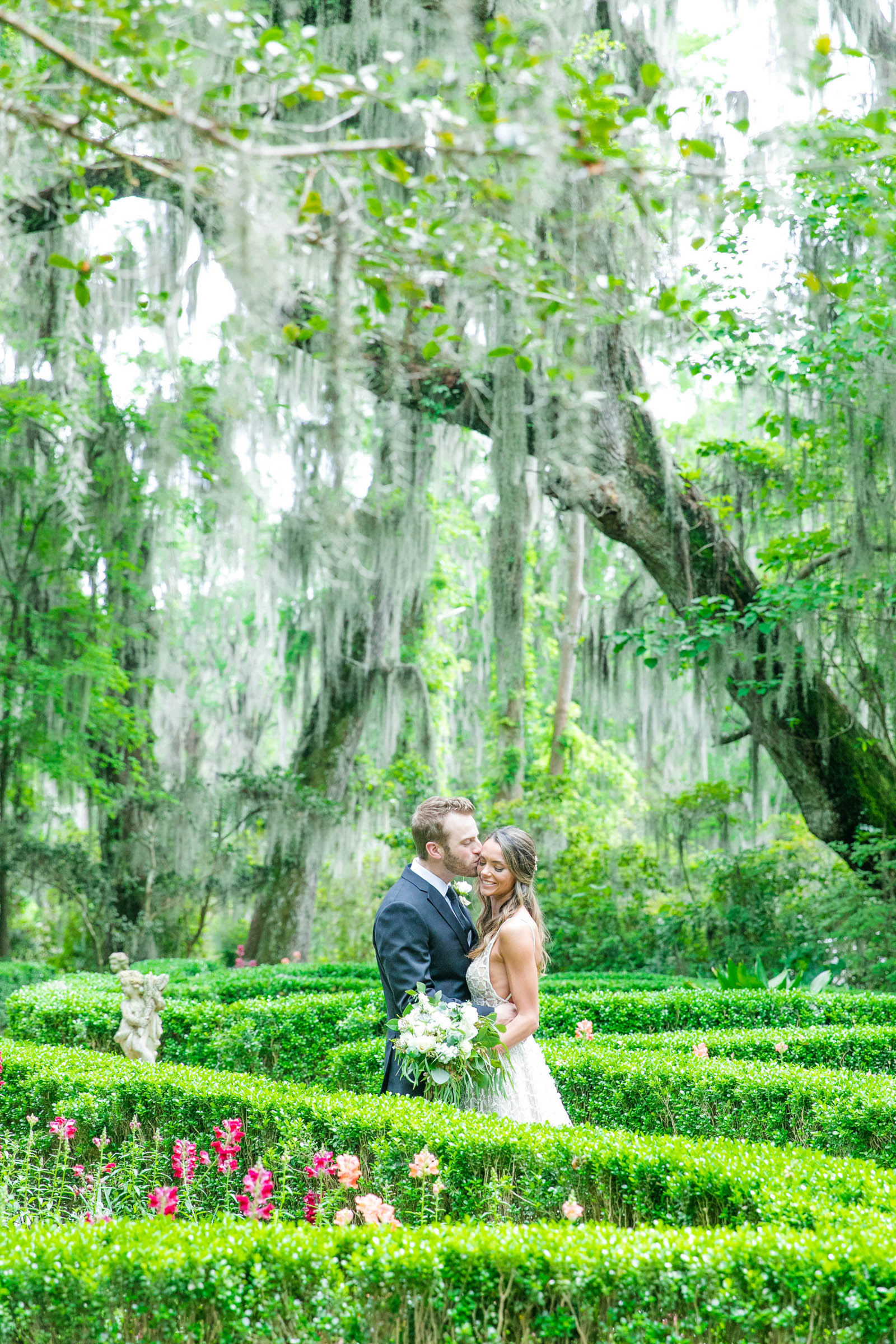 Couple kiss under spanish moss - photo by Dana Cubbage Weddings