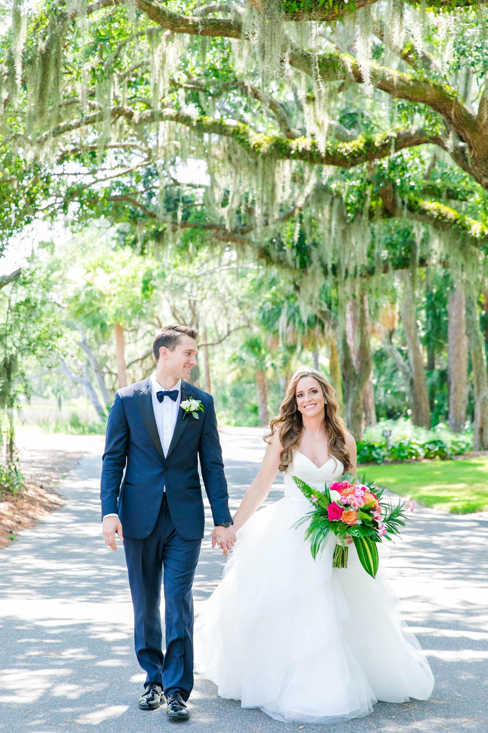 Couple walk under spanish moss - photo by Dana Cubbage Weddings