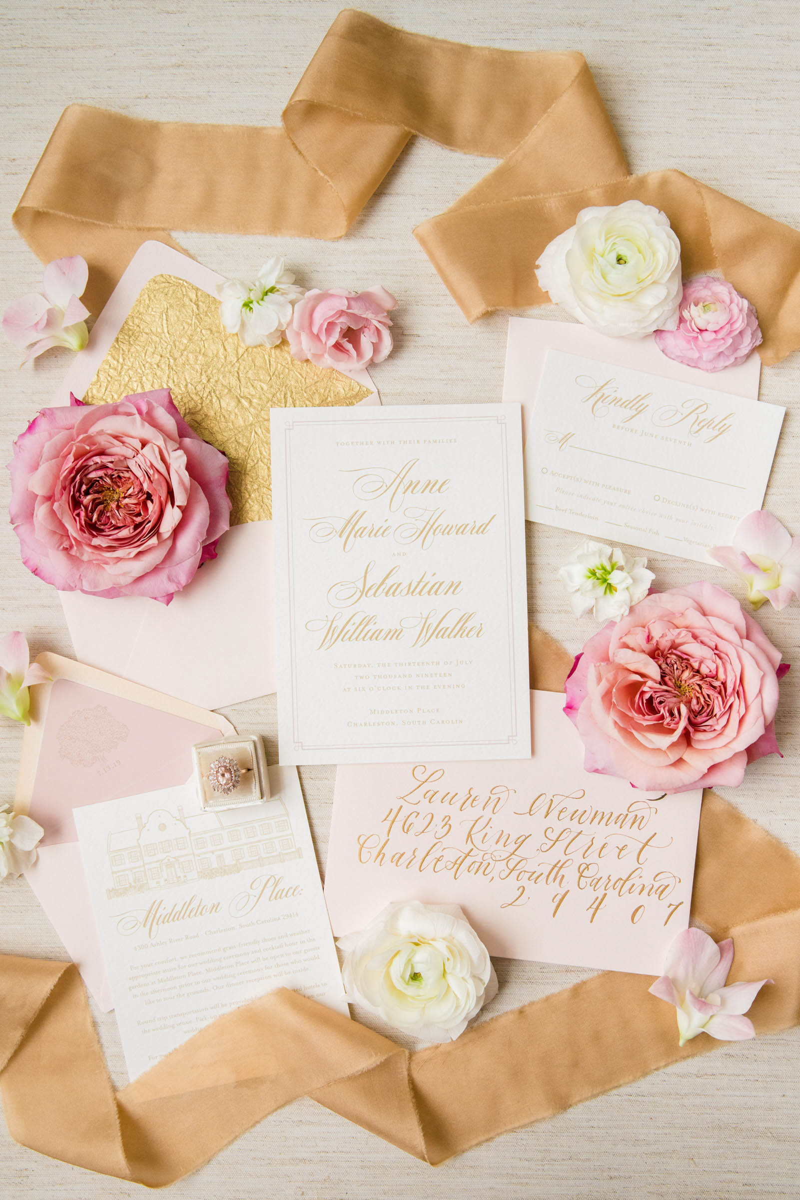 Flat lay including invitations envelopes roses ribbons - photo by Dana Cubbage Weddings