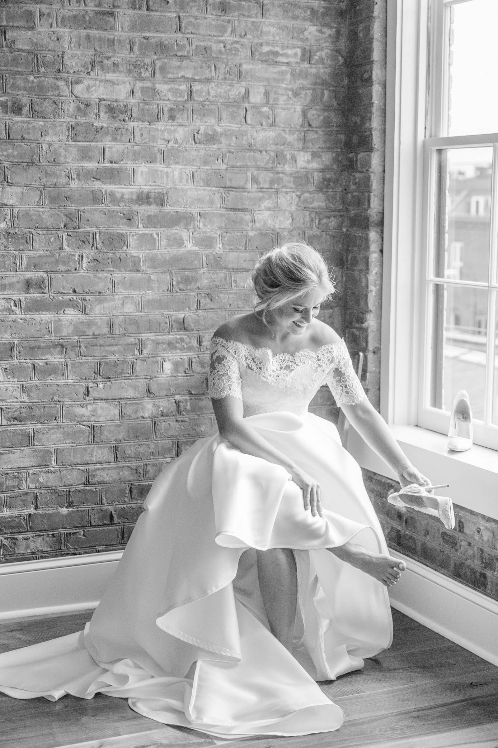 Light and airy shot of bride putting on shoes - photo by Dana Cubbage Weddings