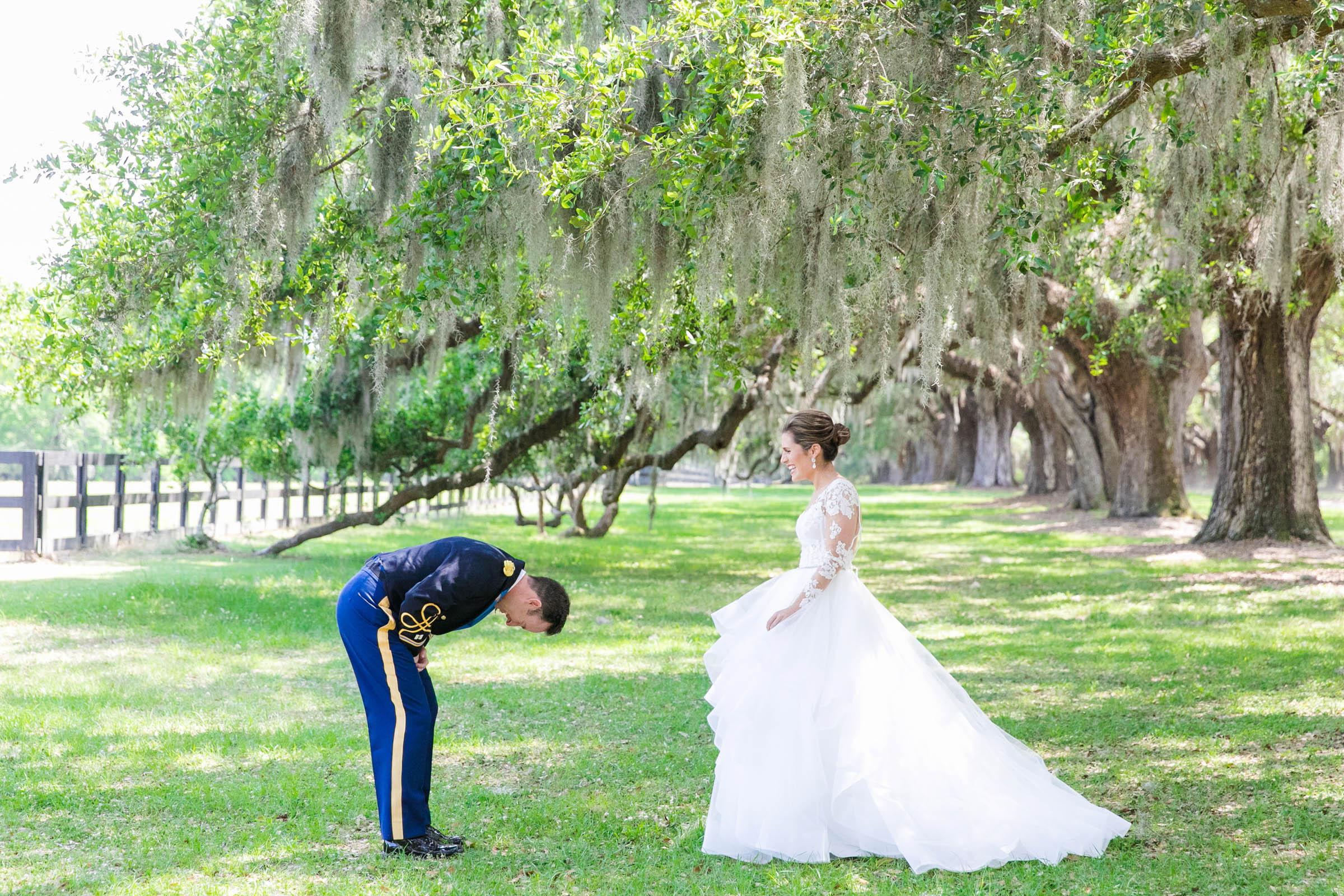 Military groom bends before elegant bride - photo by Dana Cubbage Weddings