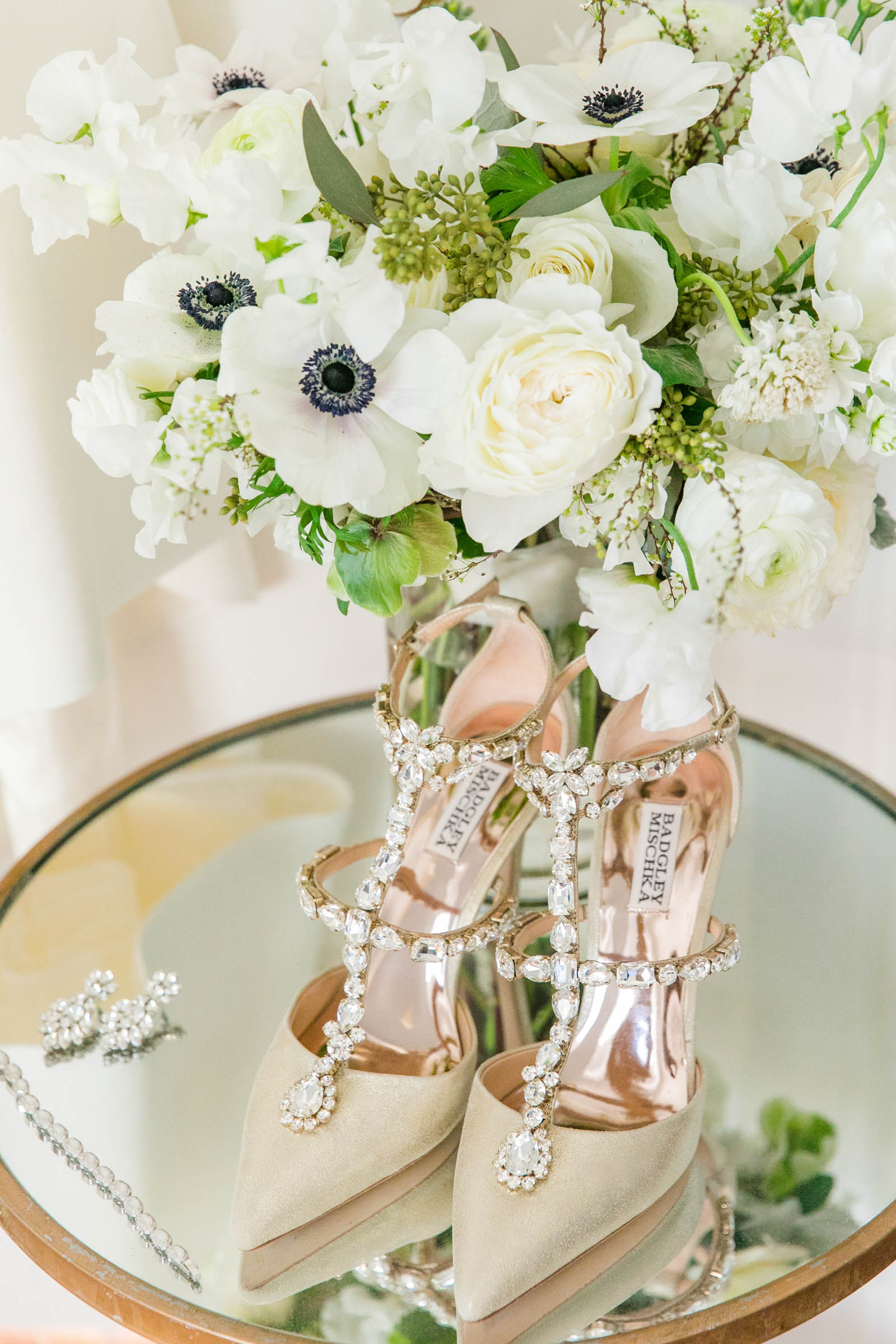 Shoes and earrings with bouquet in mirror - photo by Dana Cubbage Weddings