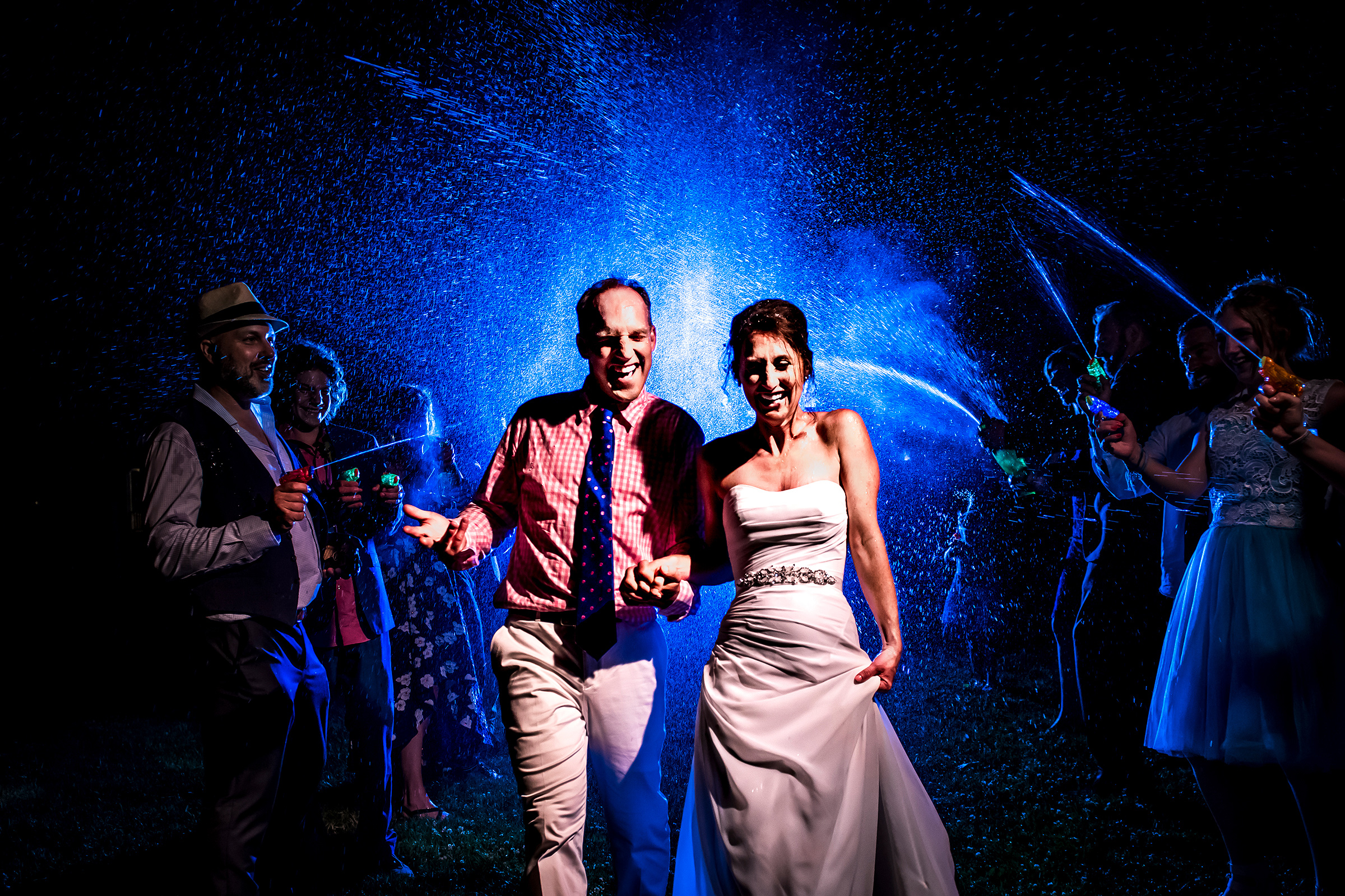 Bride and groom during water gun exit - photo by J. La Plante Photo
