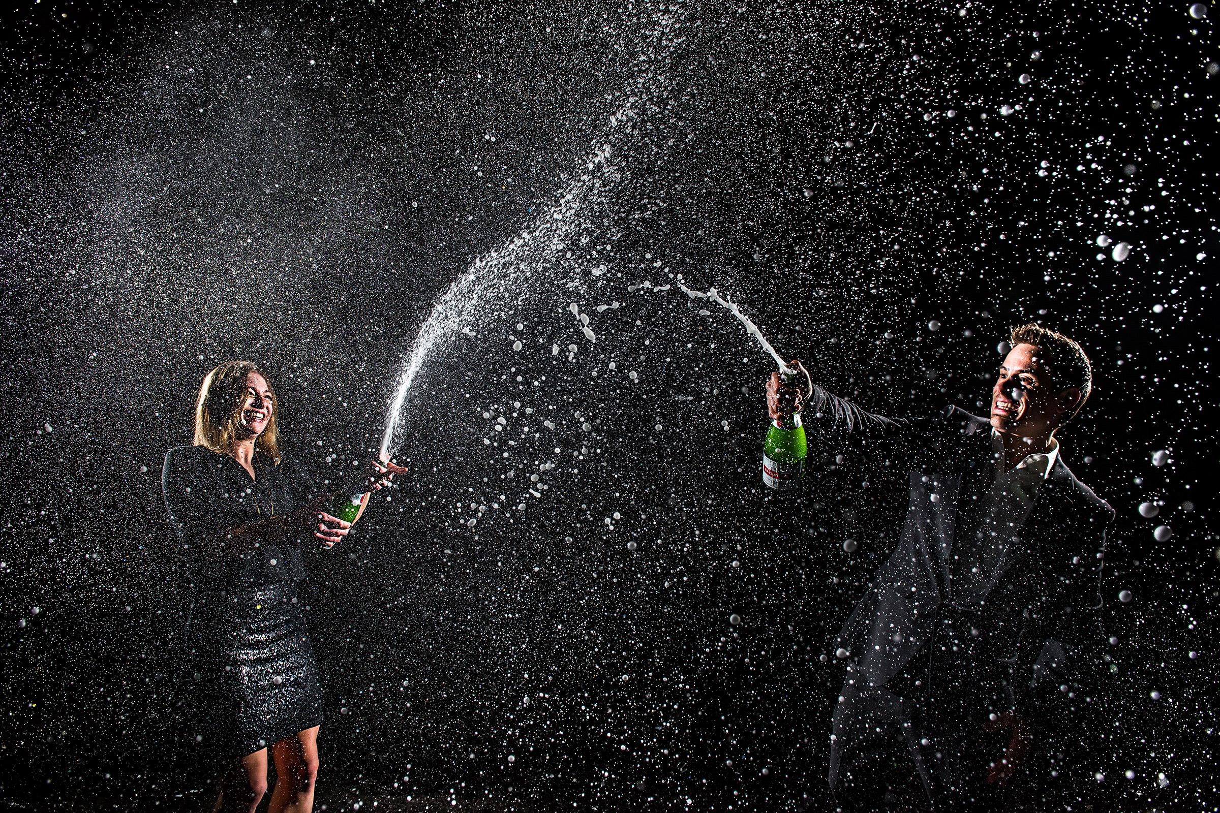 Couple spraying champagne - photo by J. La Plante Photo