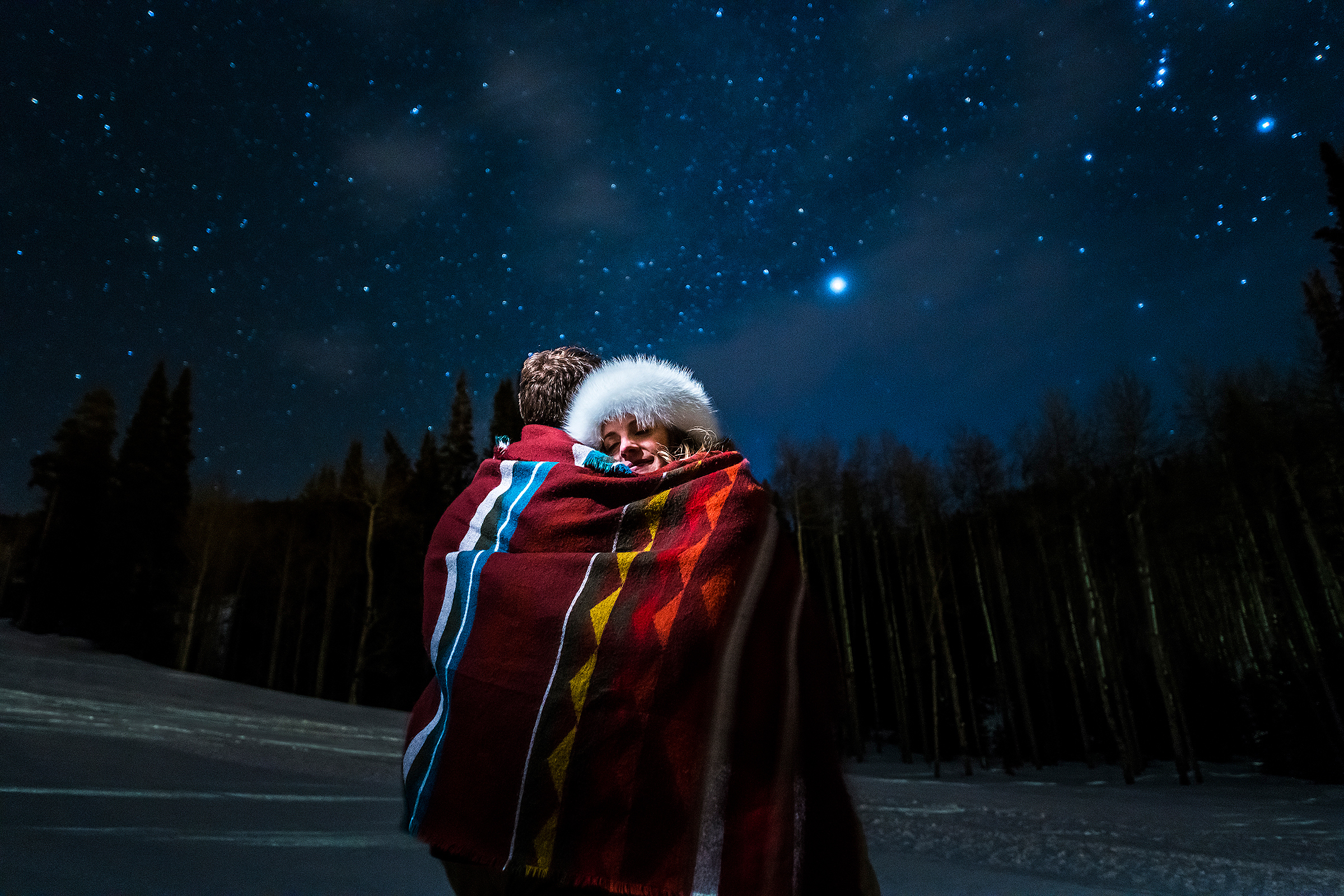 couple wrapped in blanked under northern lights sky - photo by J La Plante Photo