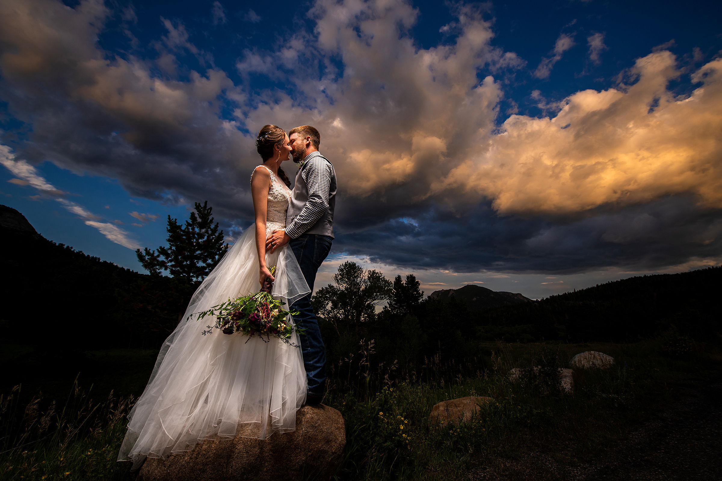 Creative composition of bride and groom against dramatic sky - photo by J La Plante Photo