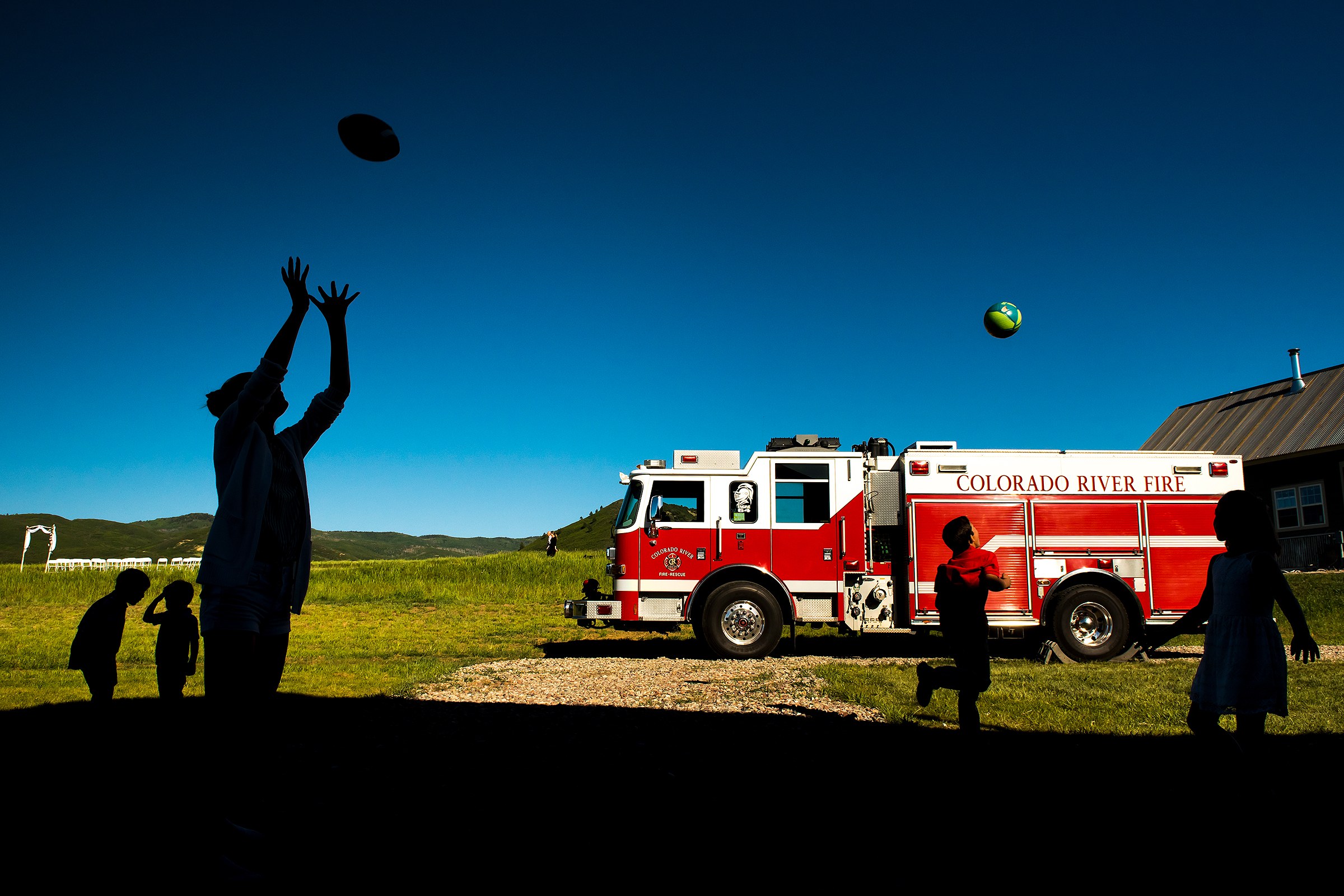Firetruck and playing children in foreground of ceremony site - photo by J La Plante Photo