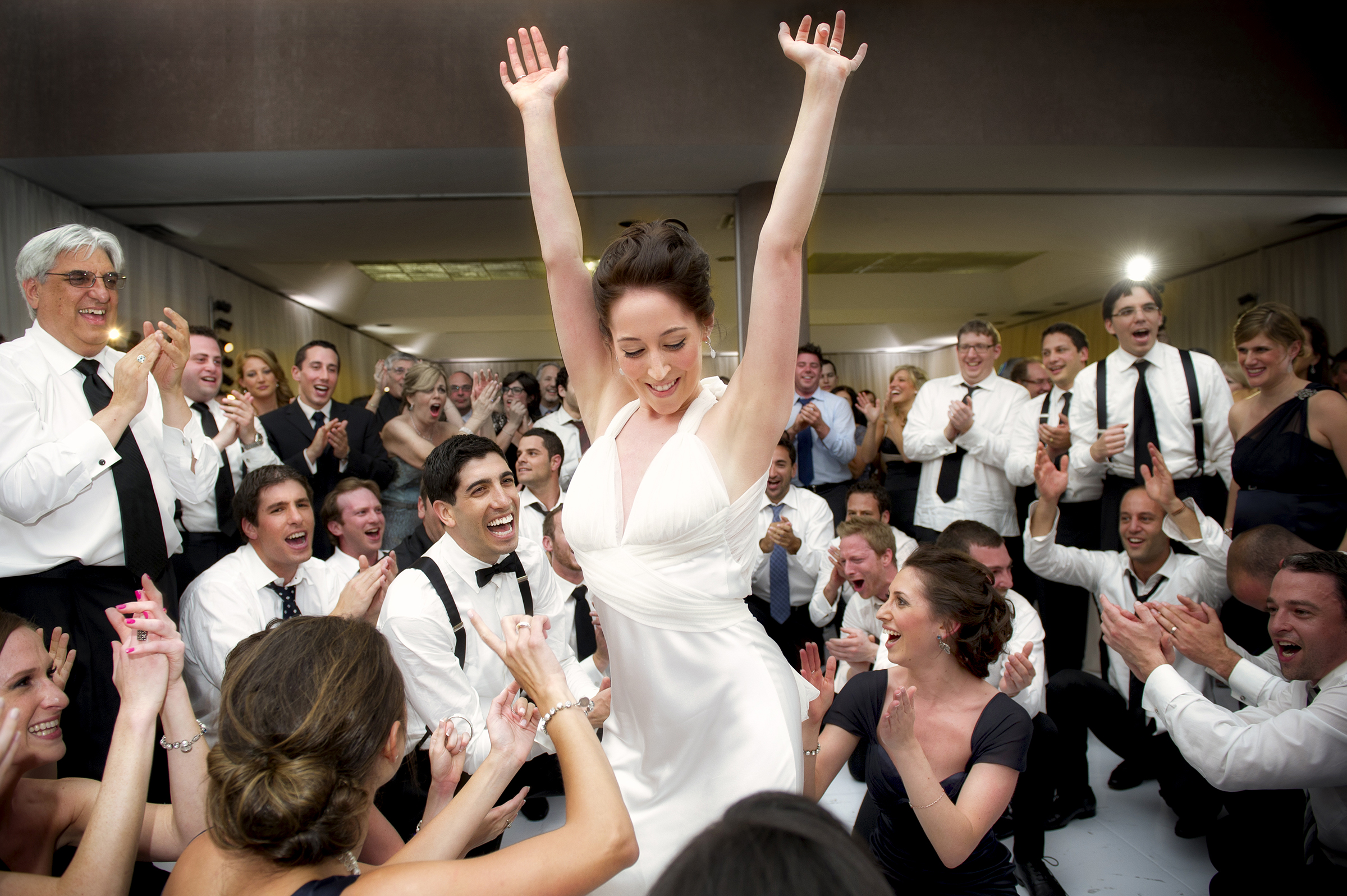 Bride dancing arms up amid guests - photo by Storey Wilkins Photography