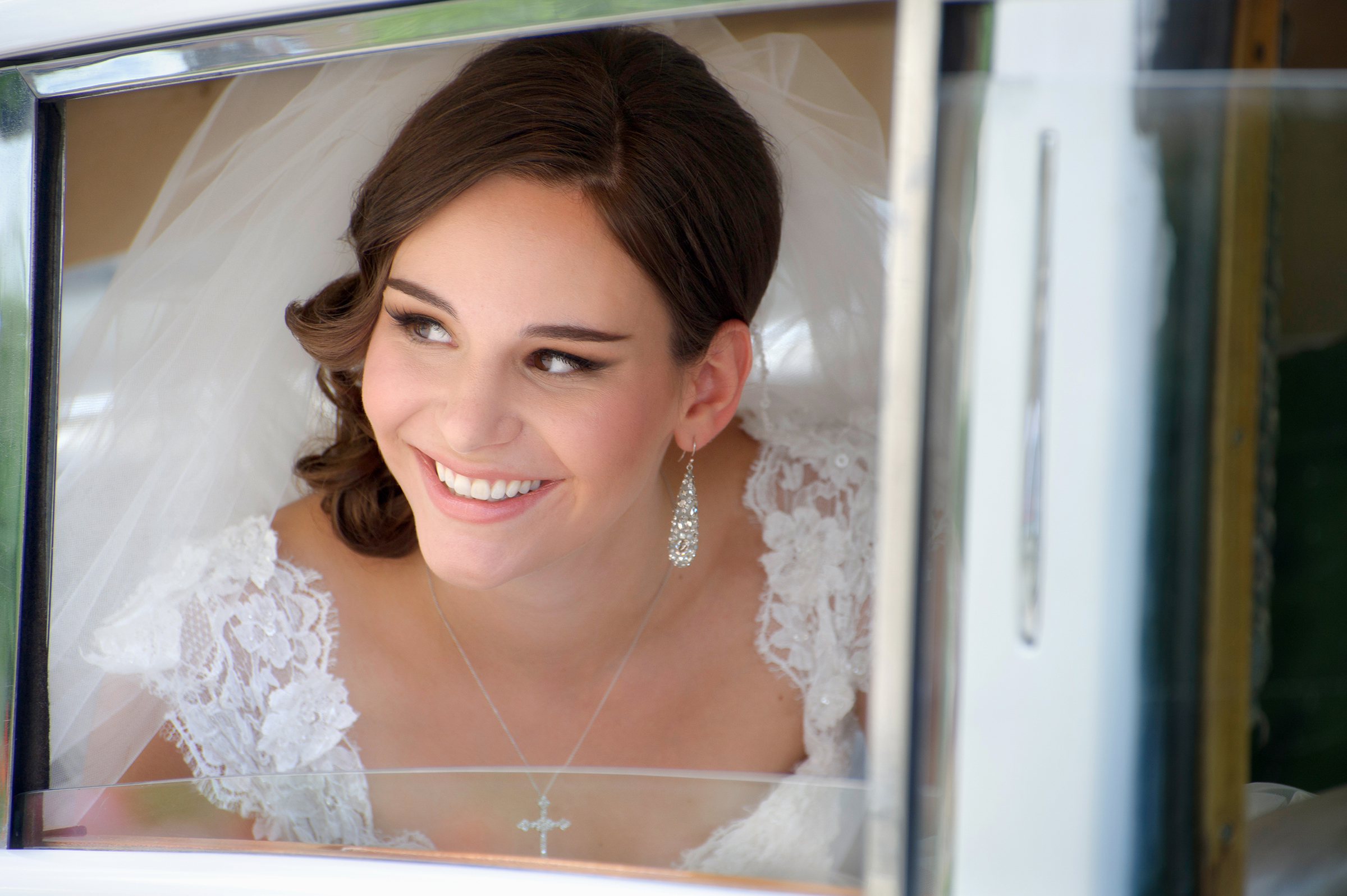 Bride seen through limo window - photo by Storey Wilkins Photography