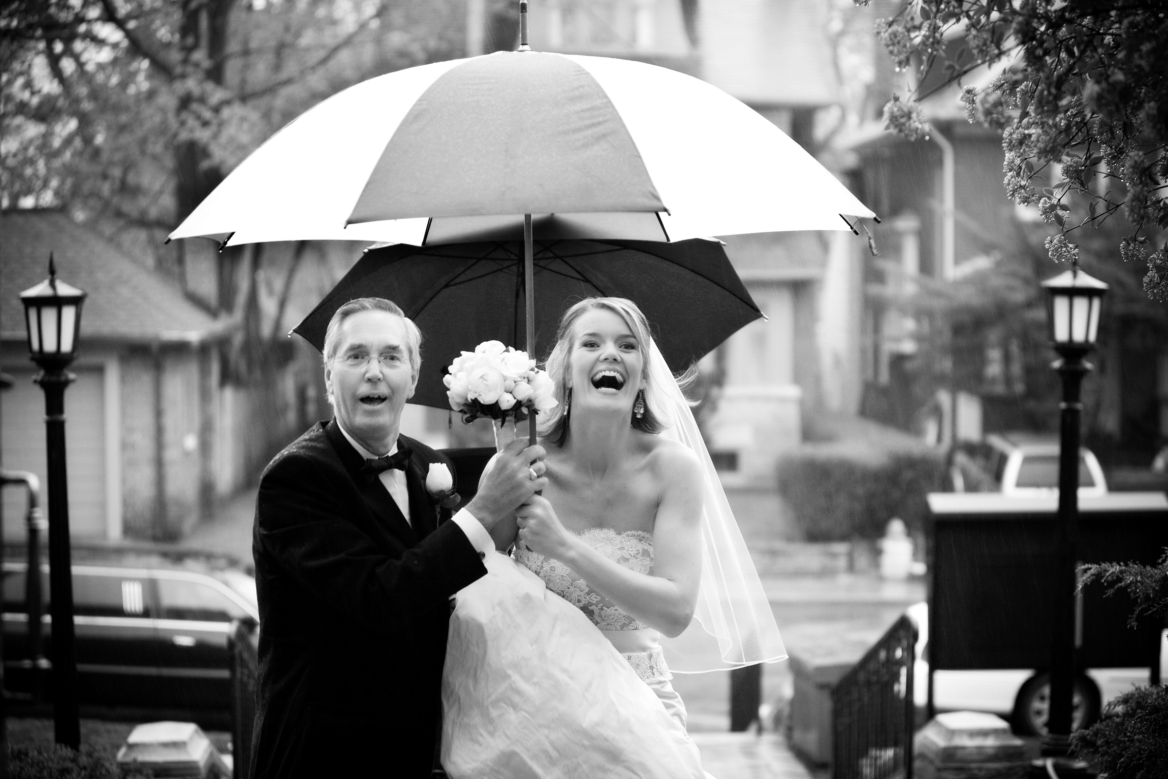 Under umbrellas bride and father approach - photo by Storey Wilkins Photography
