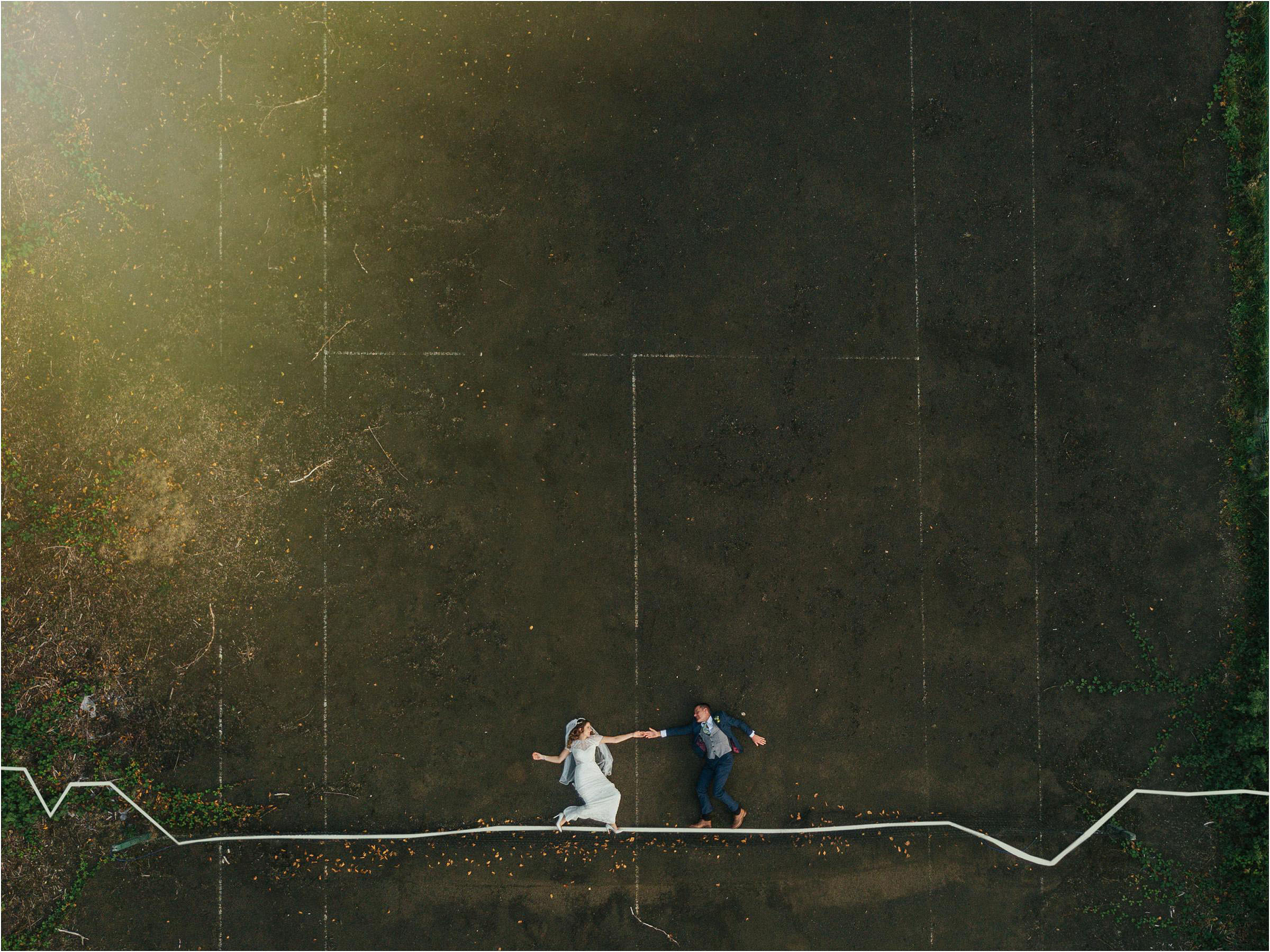 Aerial shot of couple on ground - photo by The Crawleys