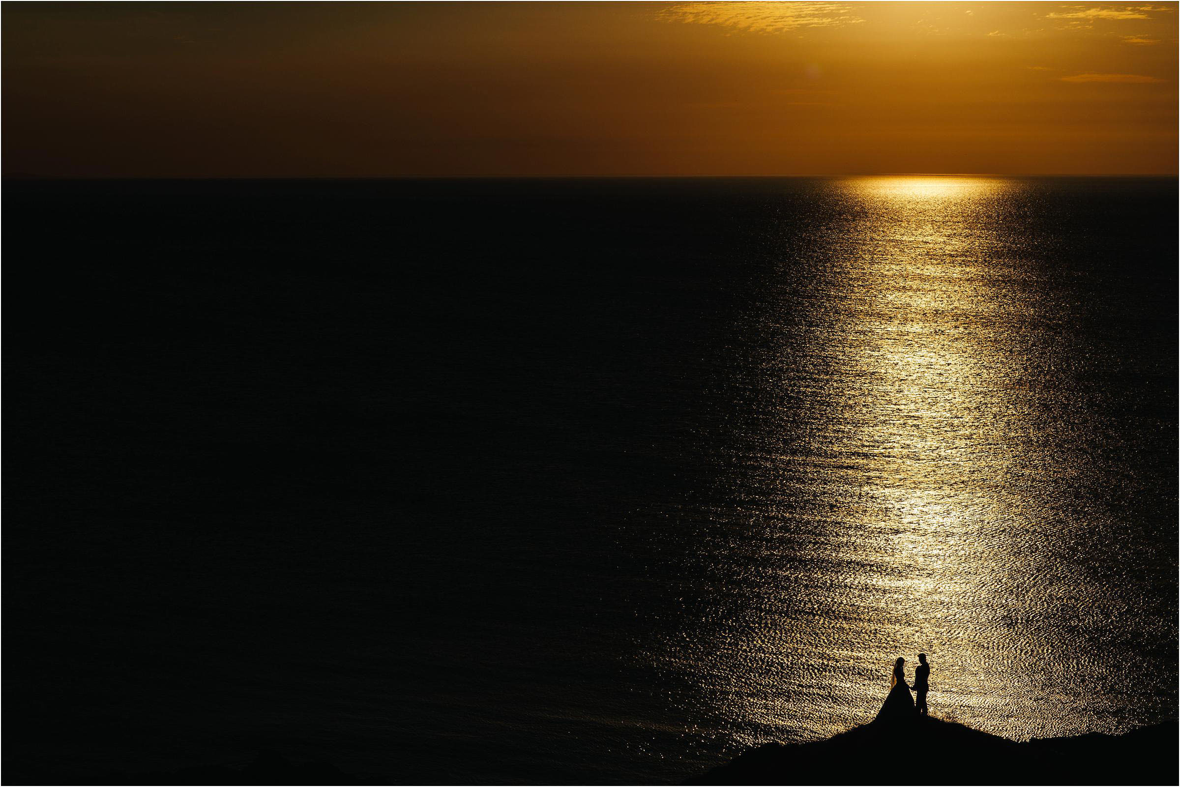 Couple beach silhouette in column of light - photo by The Crawleys