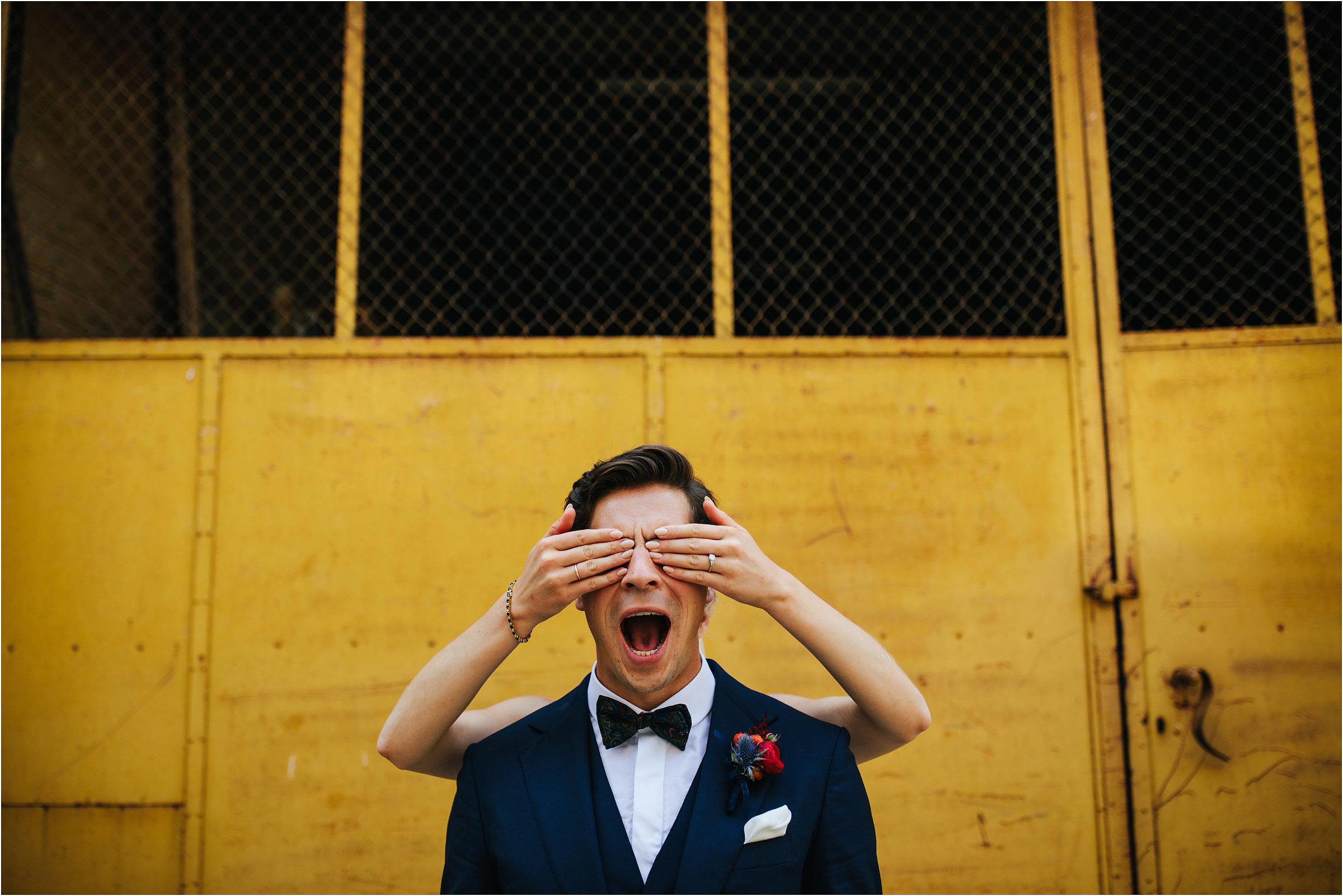 Funny shot of brides hand over grooms eyes - photo by The Crawleys
