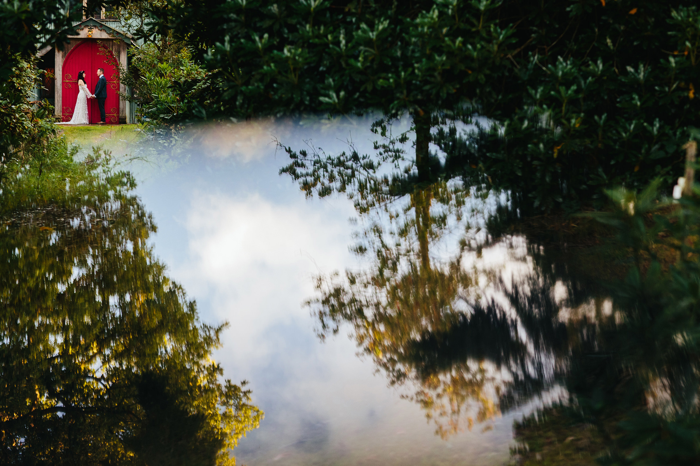 Couple in front of cottage with lake reflection at Walcot Hall Shropshire - photo by The Crawleys
