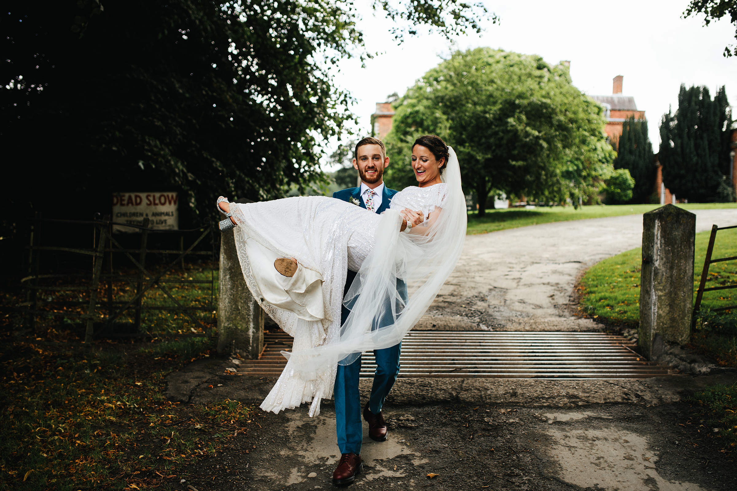 Groom carries bride over cow grate at Walcot Hall UK - photo by The Crawleys