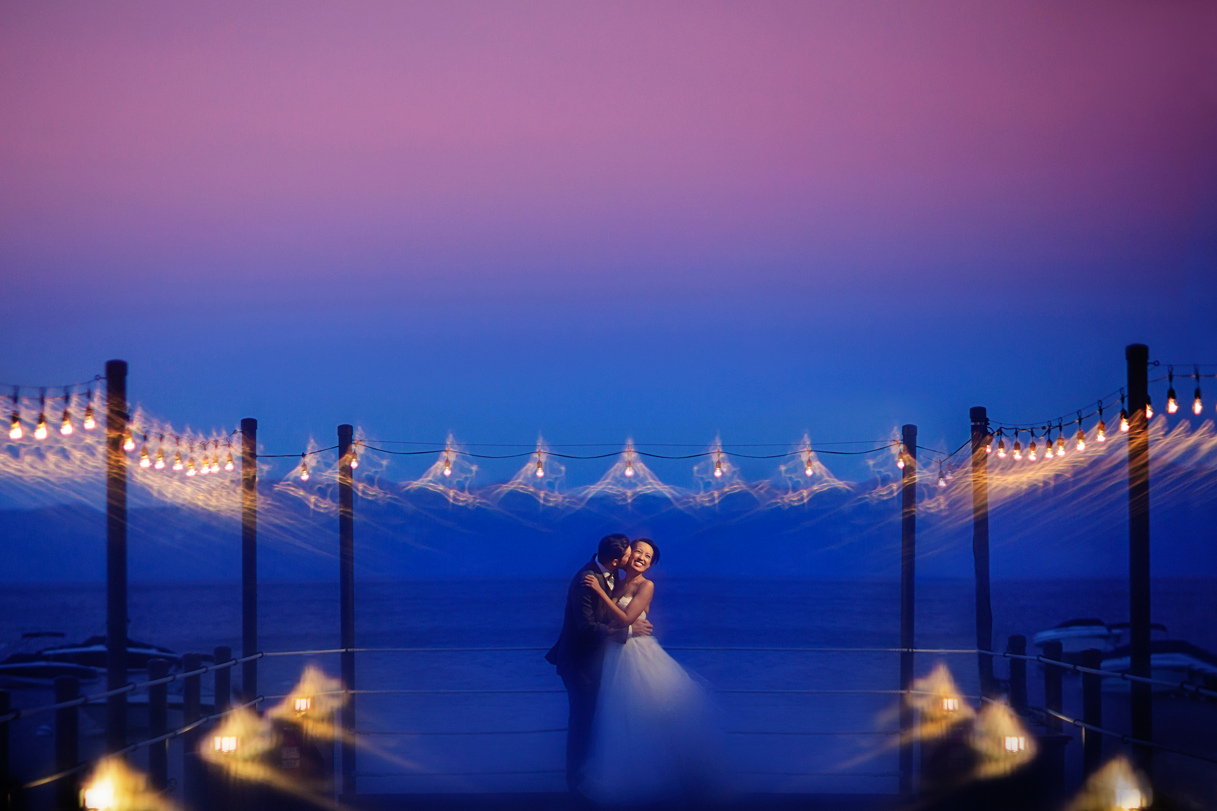 Bride and groom at dusk with slow exposure of bistro lights - photo by Chrisman Studios