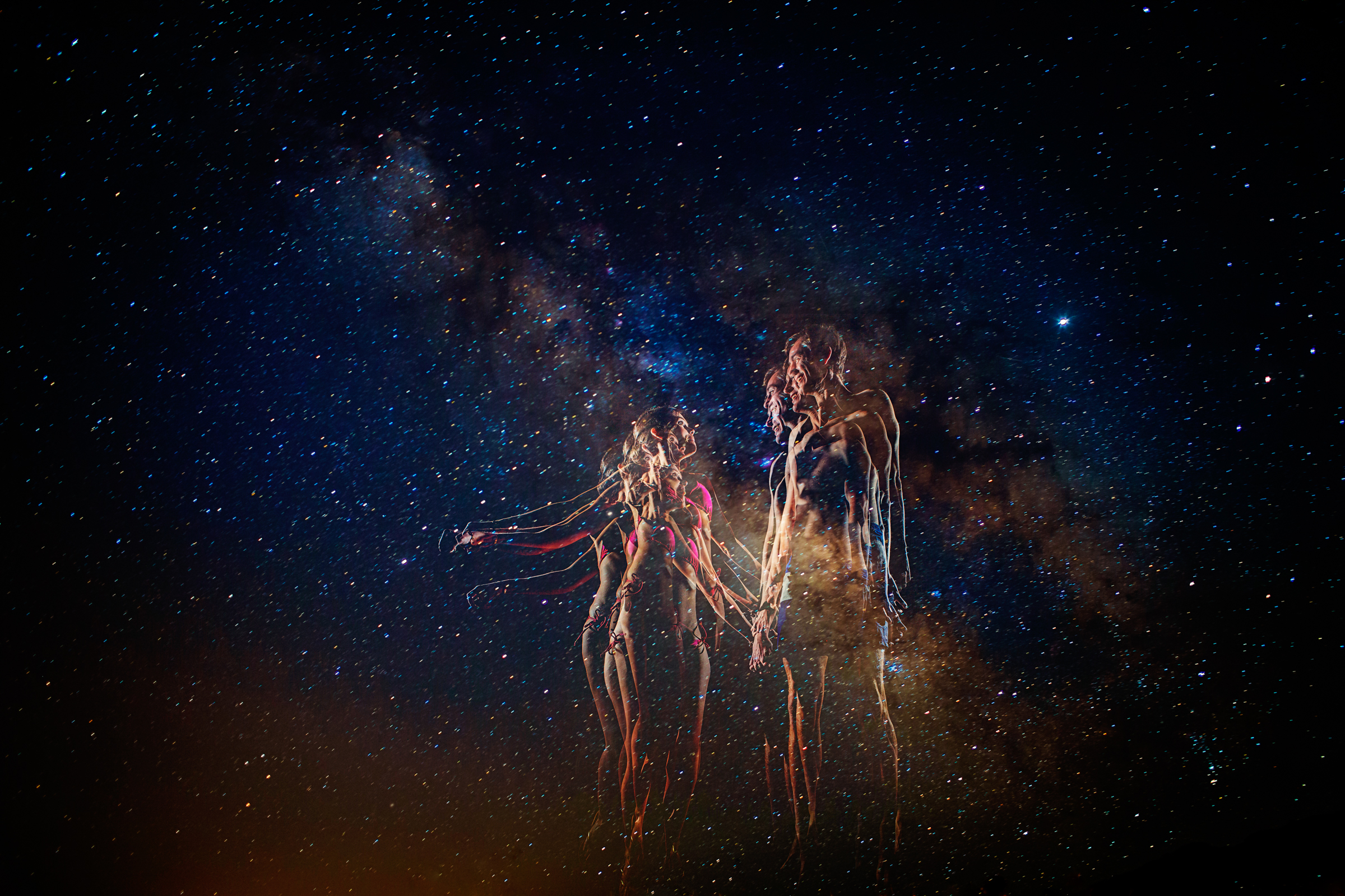 Slow exposure of couple outlined by lights against night sky - photo by Chrisman Studios