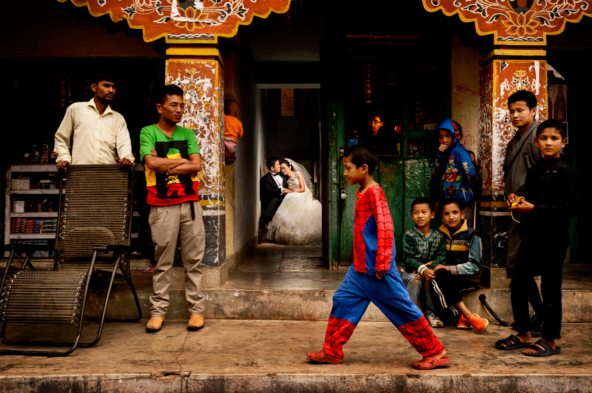 Bride and groom portrait amidst busy street scene in Bhutan - photo by Chrisman Studios