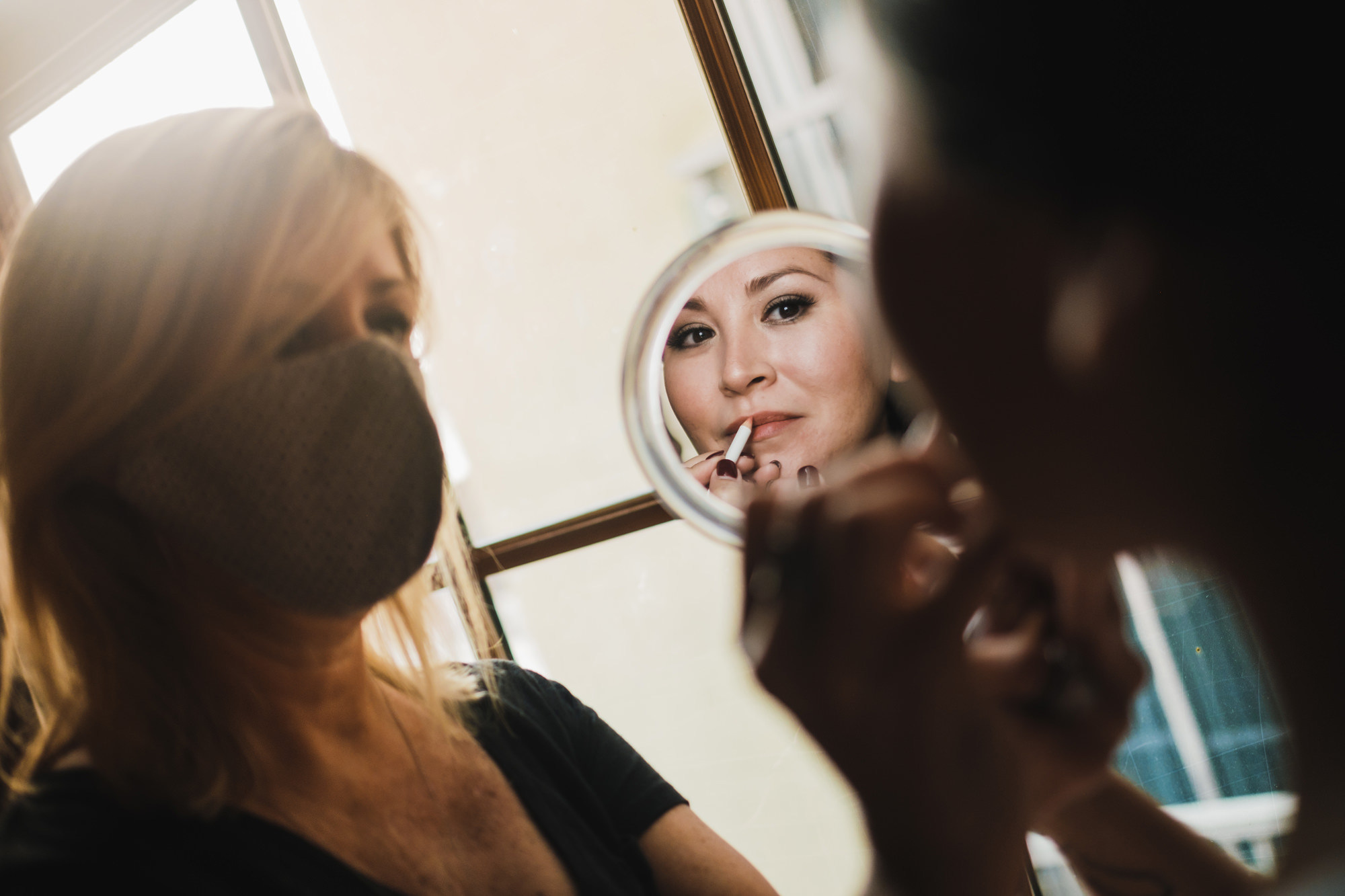 bride getting her makeup on by makeup artist with mask- photo by Chrisman Studios, charleston, restoration