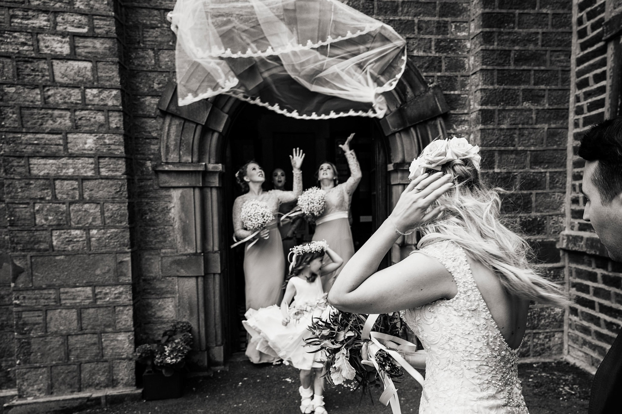 Bridesmaid in church archway attempt to catch brides veil - photo by Andrew Billington Photography