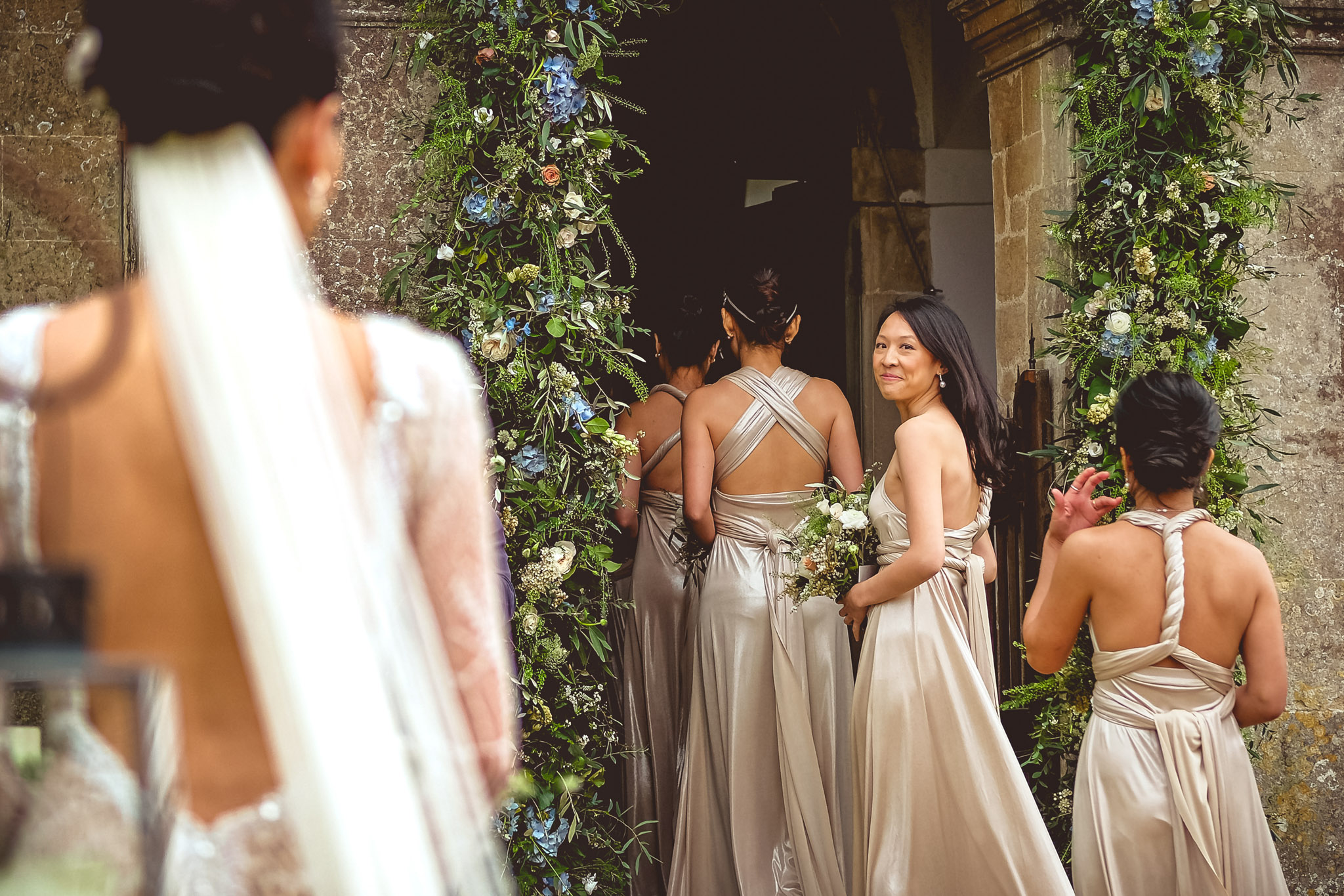 Bridesmaid ooks back at bride from processional - photo by Andrew Billington Photography