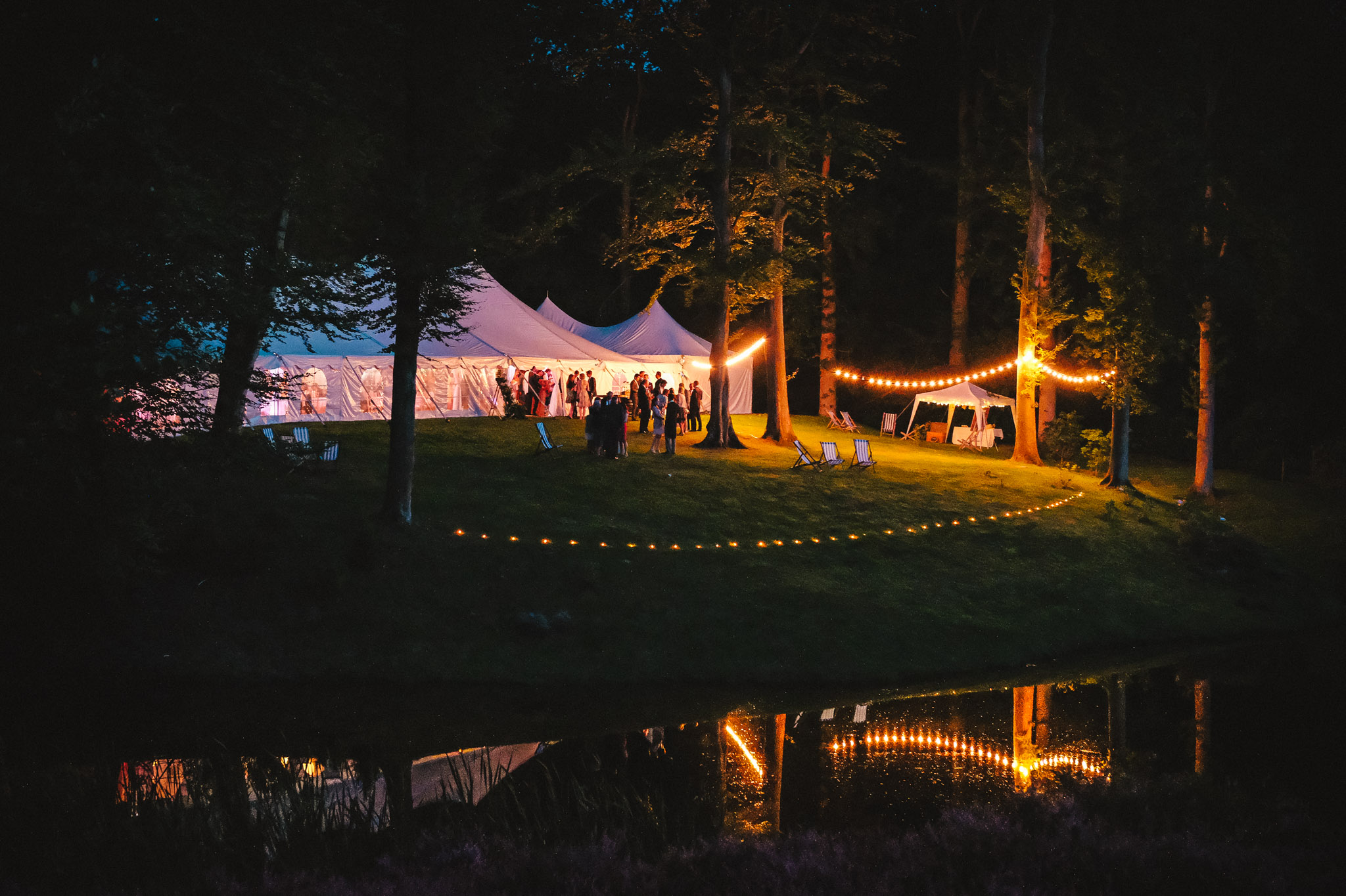 Forest lakeside wedding reception in lighted tent- photo by Andrew Billington Photography
