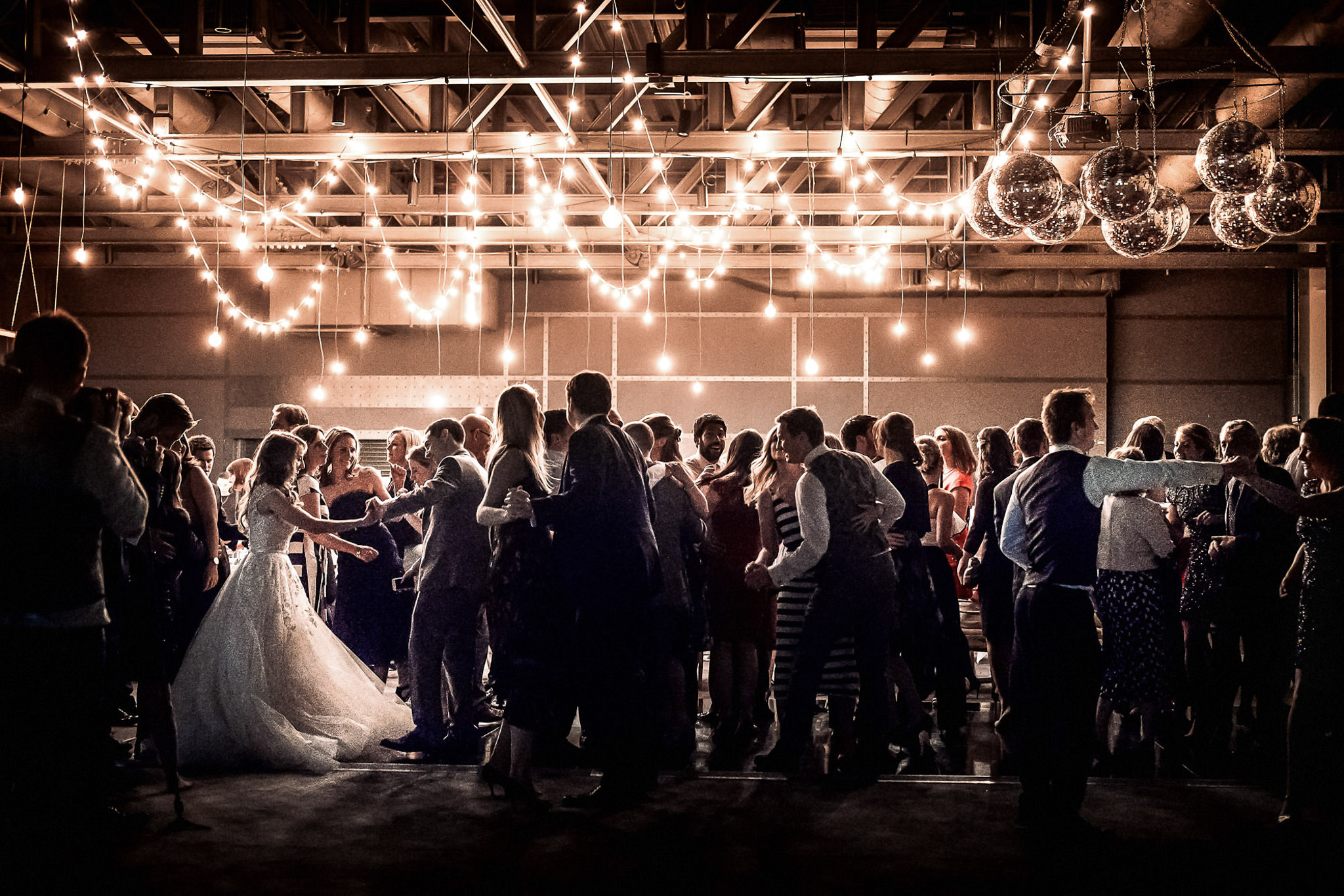 Groom spins bride on dance floor with friends - photo by Andrew Billington Photography
