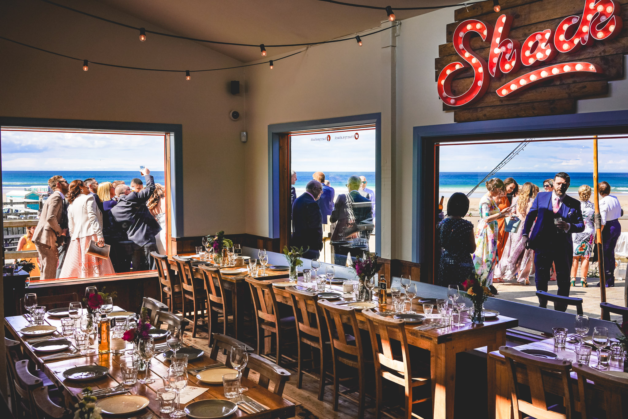 Wedding reception seen through window of seaside reception - photo by Andrew Billington Photography