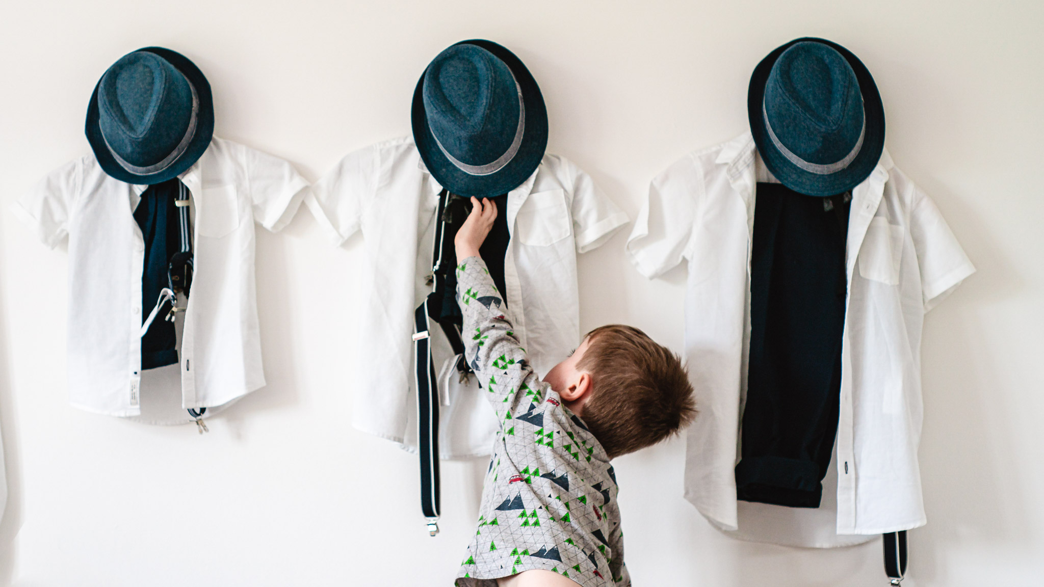 Boy reaching for his hat- photo by Andrew Billington Photography