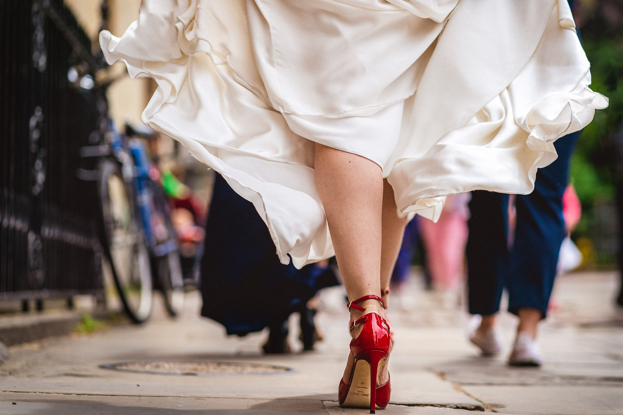 Closeup of bride walking in red shoes - photo by Andrew Billington Photography