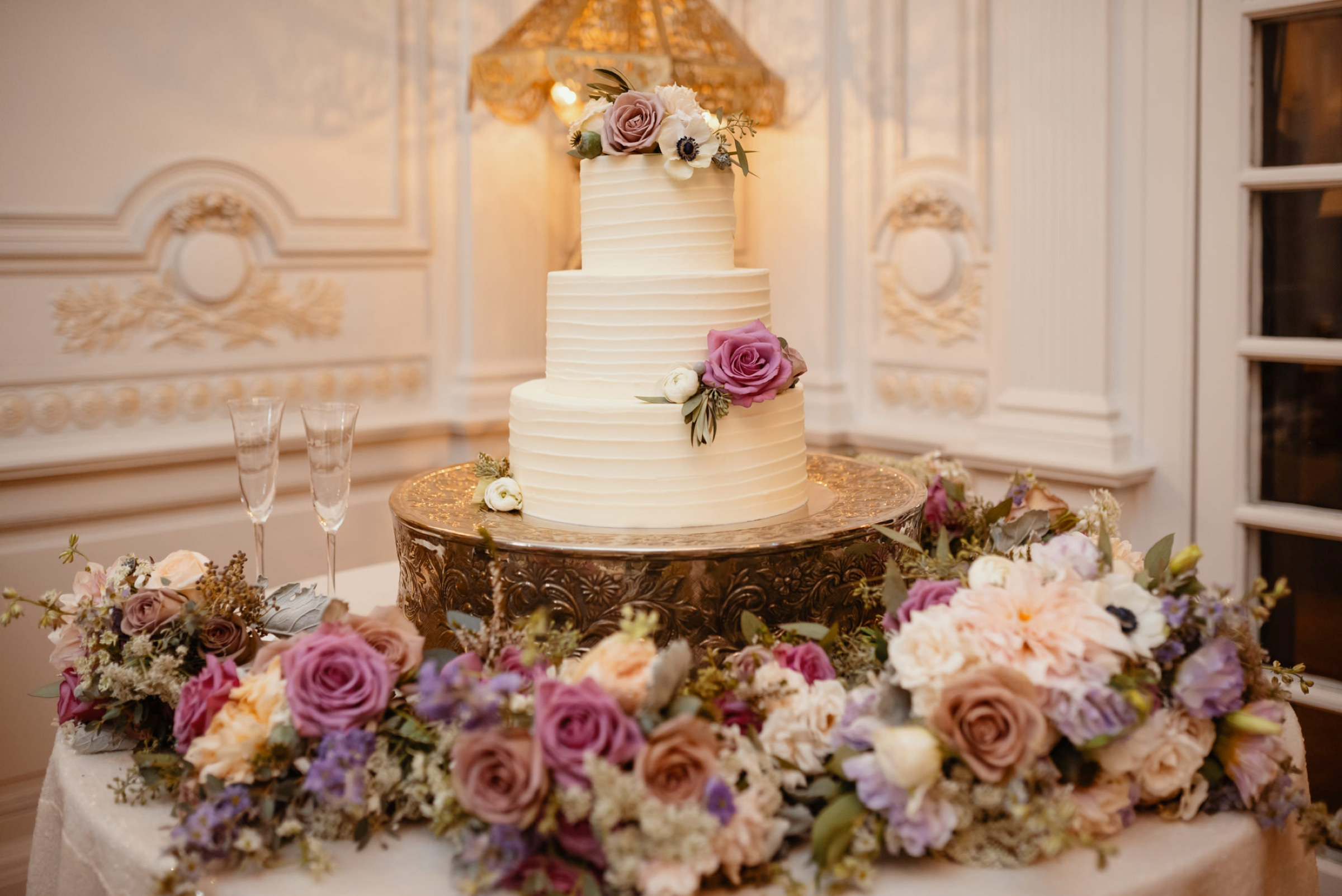 bouquets surrounding white wedding cake at reception- photo by Dark Roux
