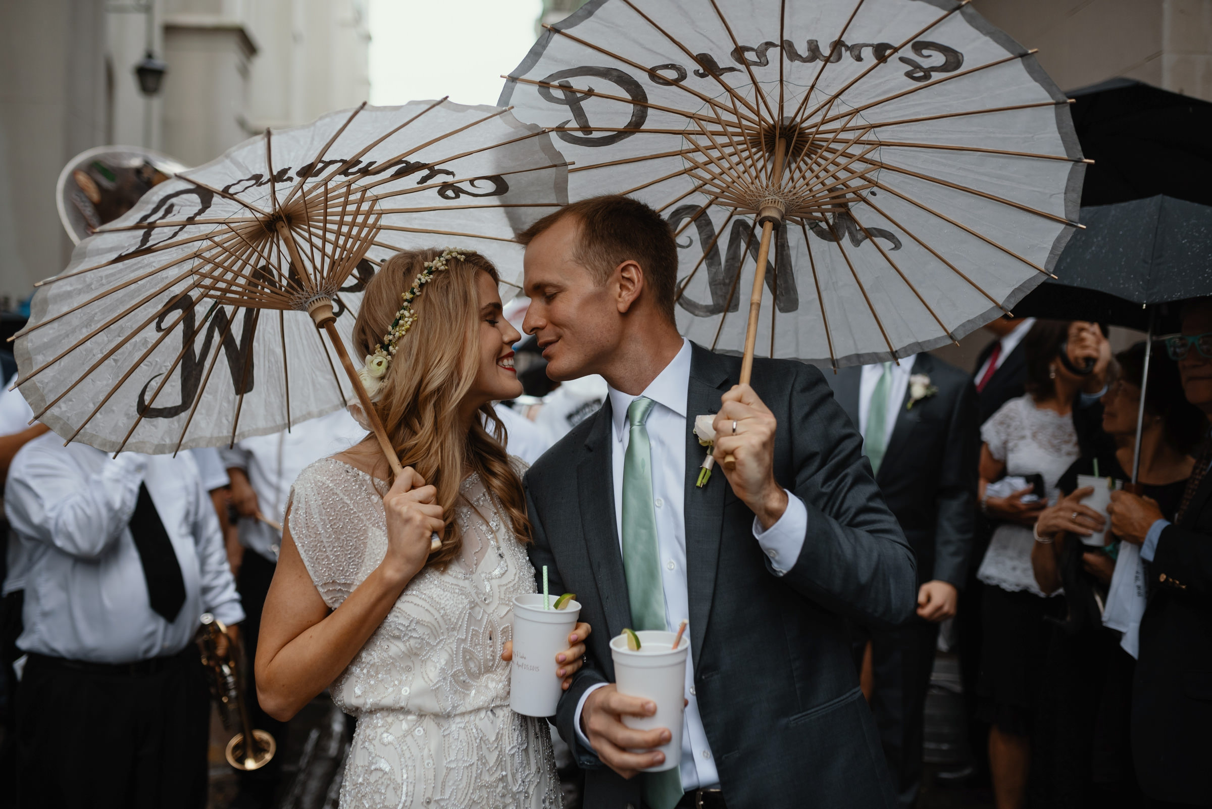 bride and groom almost kissing under their cute umbrellas - photo by Dark Roux