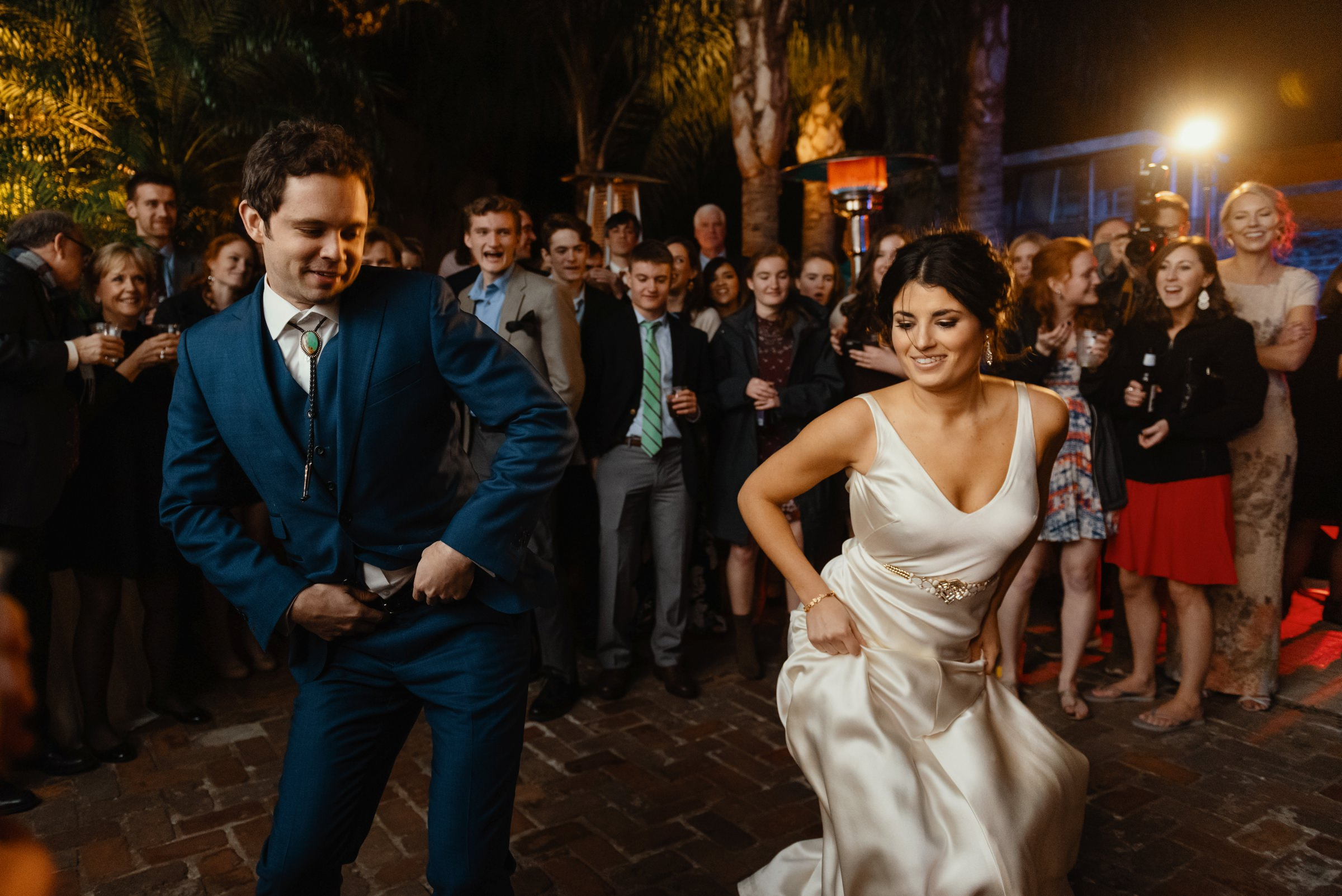 bride and groom dancing in the middle of the dance floor-groom-in-white-tuxedo-dancing-under-arms-of-groomsm- photo by Dark Roux
