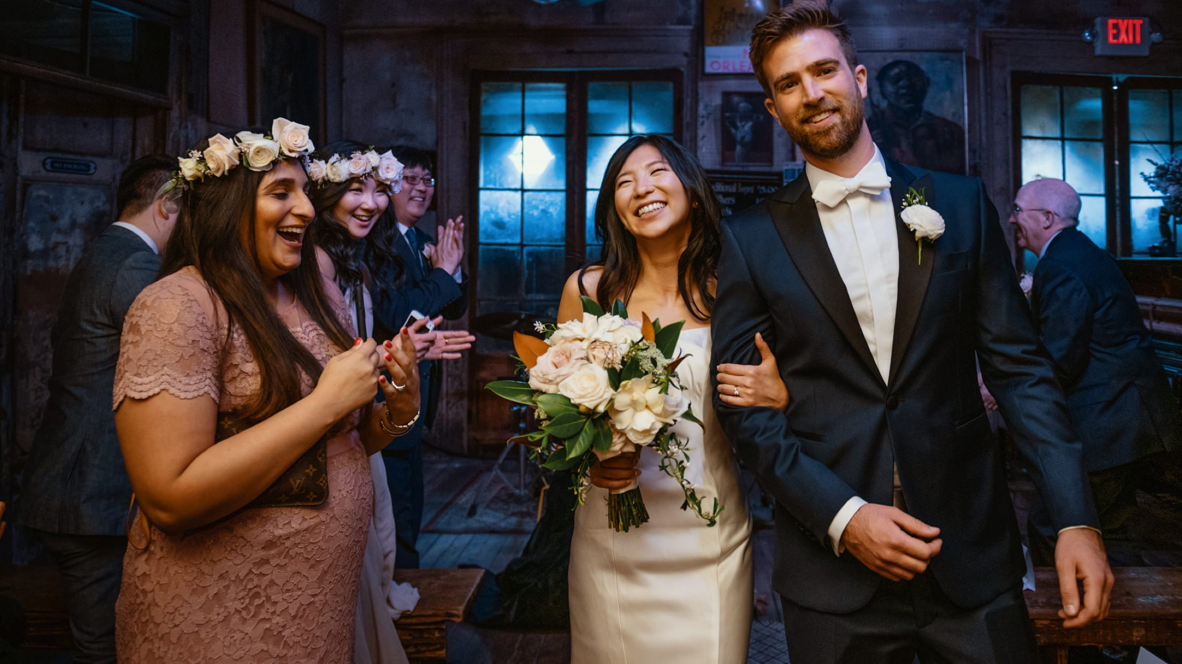 bride and groom happily walking into reception cheered by their friends-new orleans-austin-houston- photo by Dark Roux