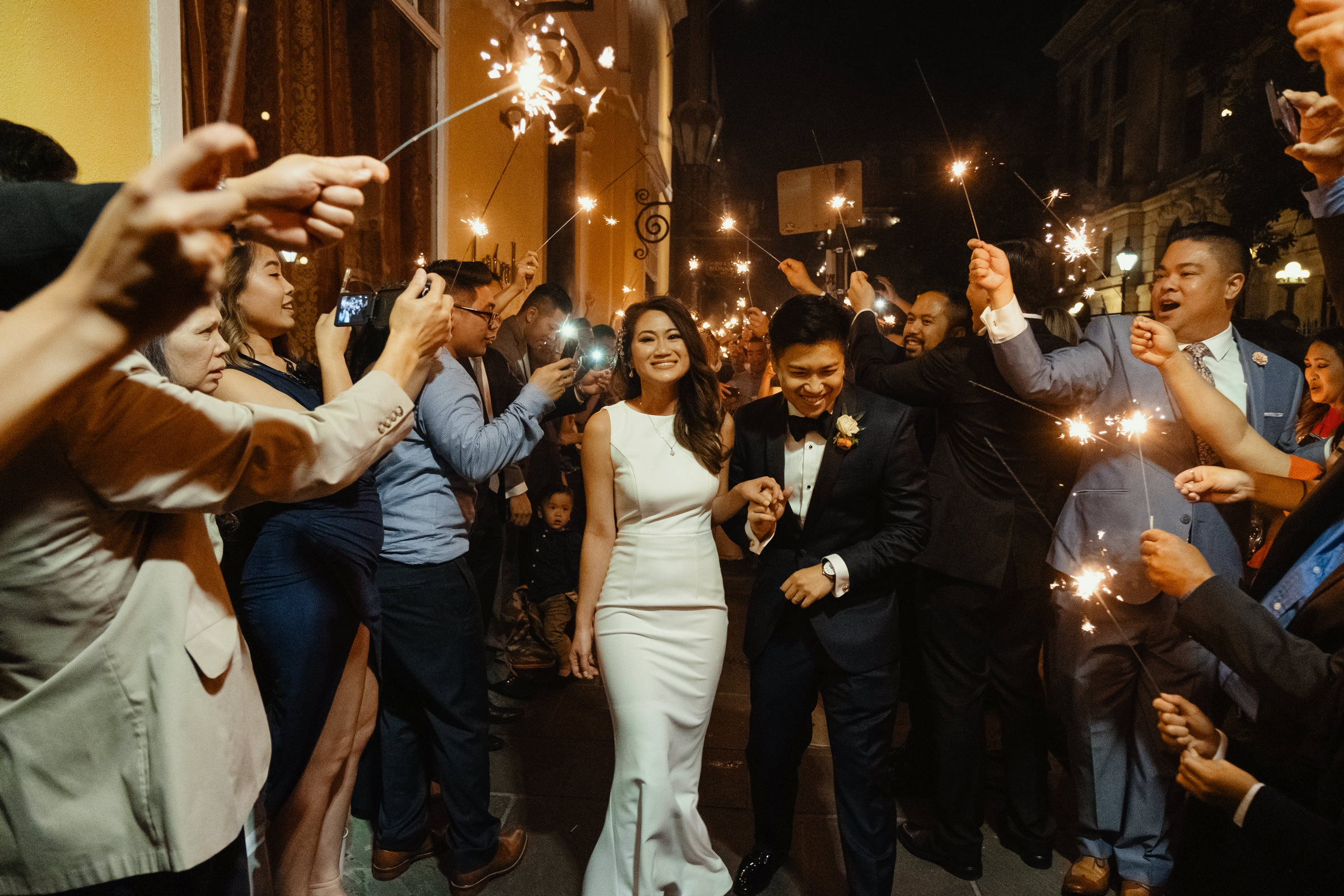 bride and groom running through a sparkler exit-new orleans-austin-houston- photo by Dark Roux